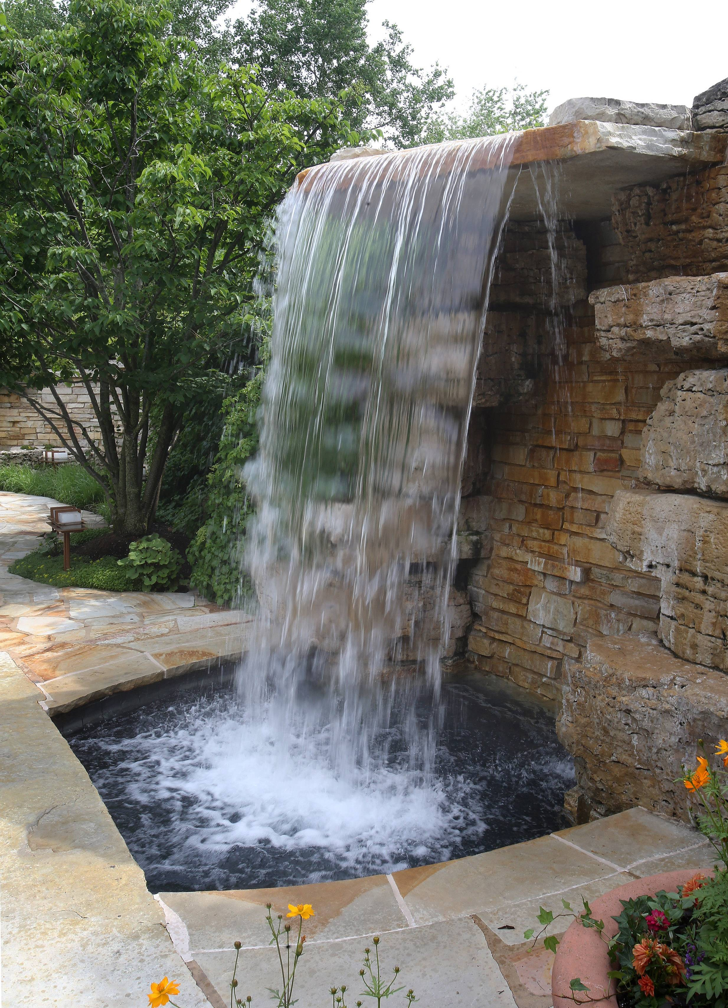 The waterfall by the swimming pool at this Barrington Hills estate enhances the sense of privacy and relaxation.