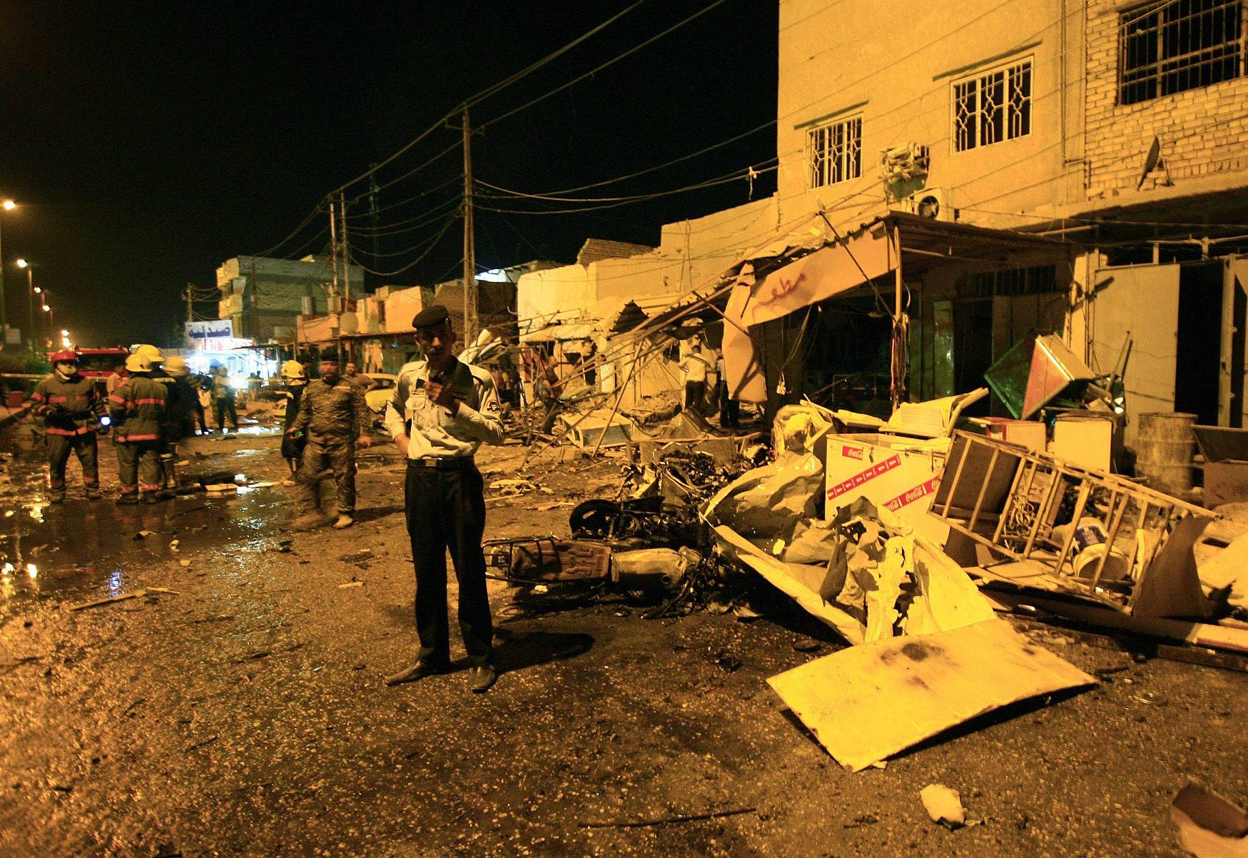 Iraqi security forces inspect the site of a car bomb attack Wednesday in Hillah, about 60 miles south of Baghdad. Iraq is experiencing its worst surge in violence since the sectarian bloodletting that nearly tore the country apart in 2006 and 2007.