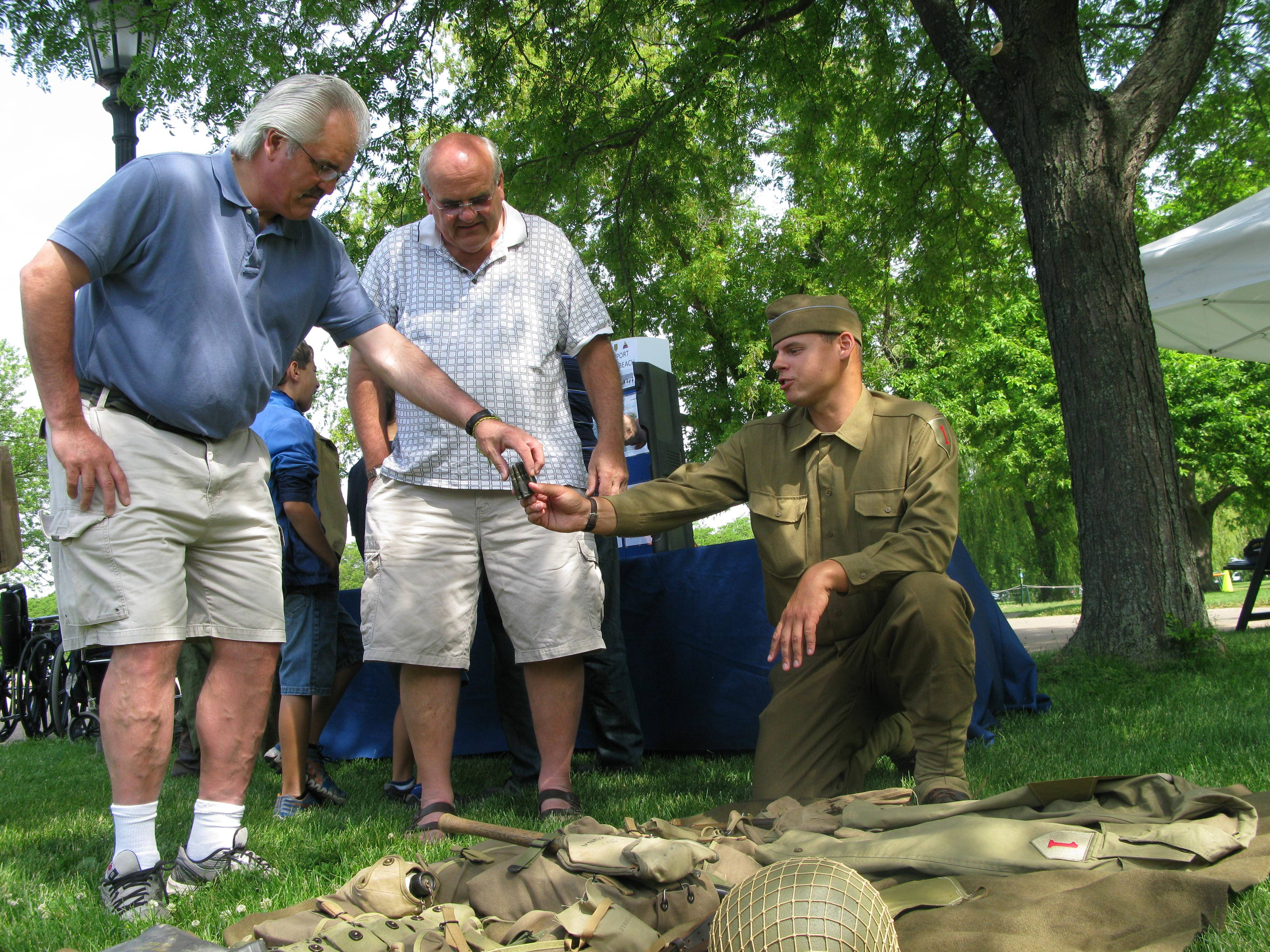 Eric Percy, right, with the Living History Detachment of the First Division Museum at Cantigny Park in Wheaton, explains ammunition carried by World War II D-Day troops to brothers Jim, left, and John Rudins of Lombard during the 70th anniversary commemoration of D-Day Saturday.