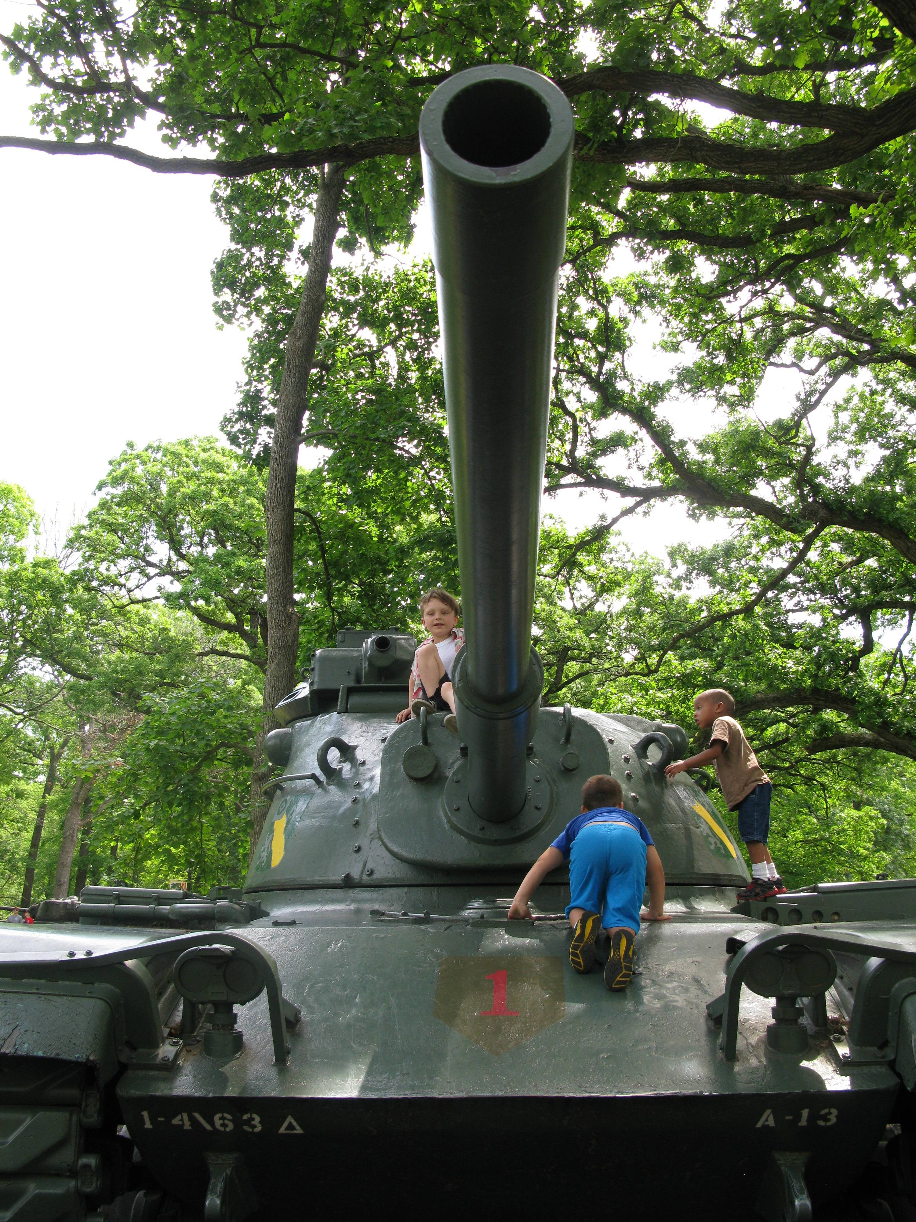 From left, William Hughes, 6, of Chicago, and brothers Cole, 5, and Miles Heerema, 4, of Oakbrook Terrace, climb up a tank Saturday at Cantigny Park in Wheaton where visitors marked the 70th anniversary commemoration of D-Day, the Allied invasion of France during World War II.