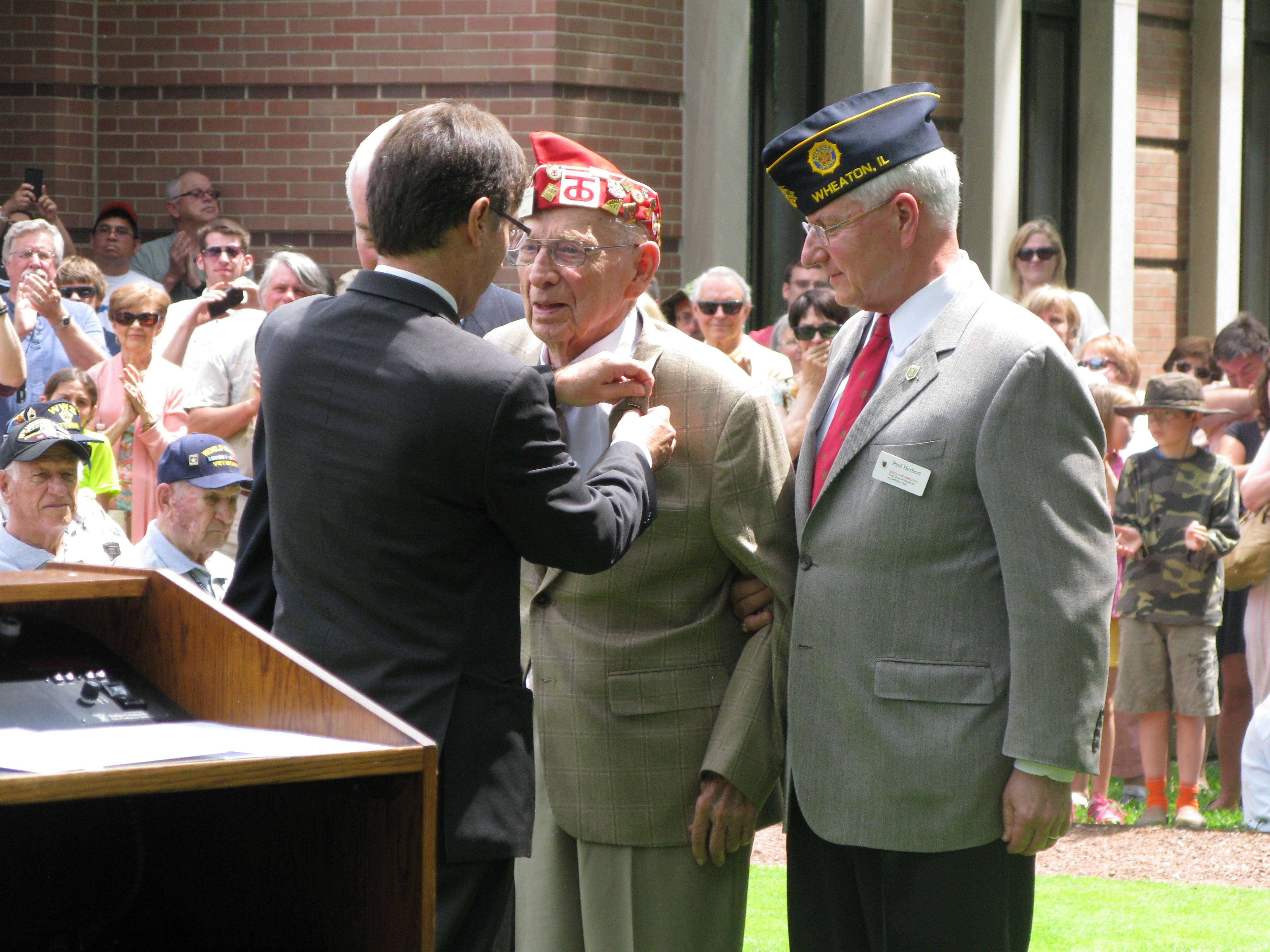 James Reid of Oak Brook, center, receives the French Legion of Honor medal Saturday from Graham Paul, consul general of France to Chicago, during the 70th anniversary commemoration of D-Day at Cantigny Park in Wheaton. To his right stands Paul Herbert, director of the First Division Museum at Cantigny.