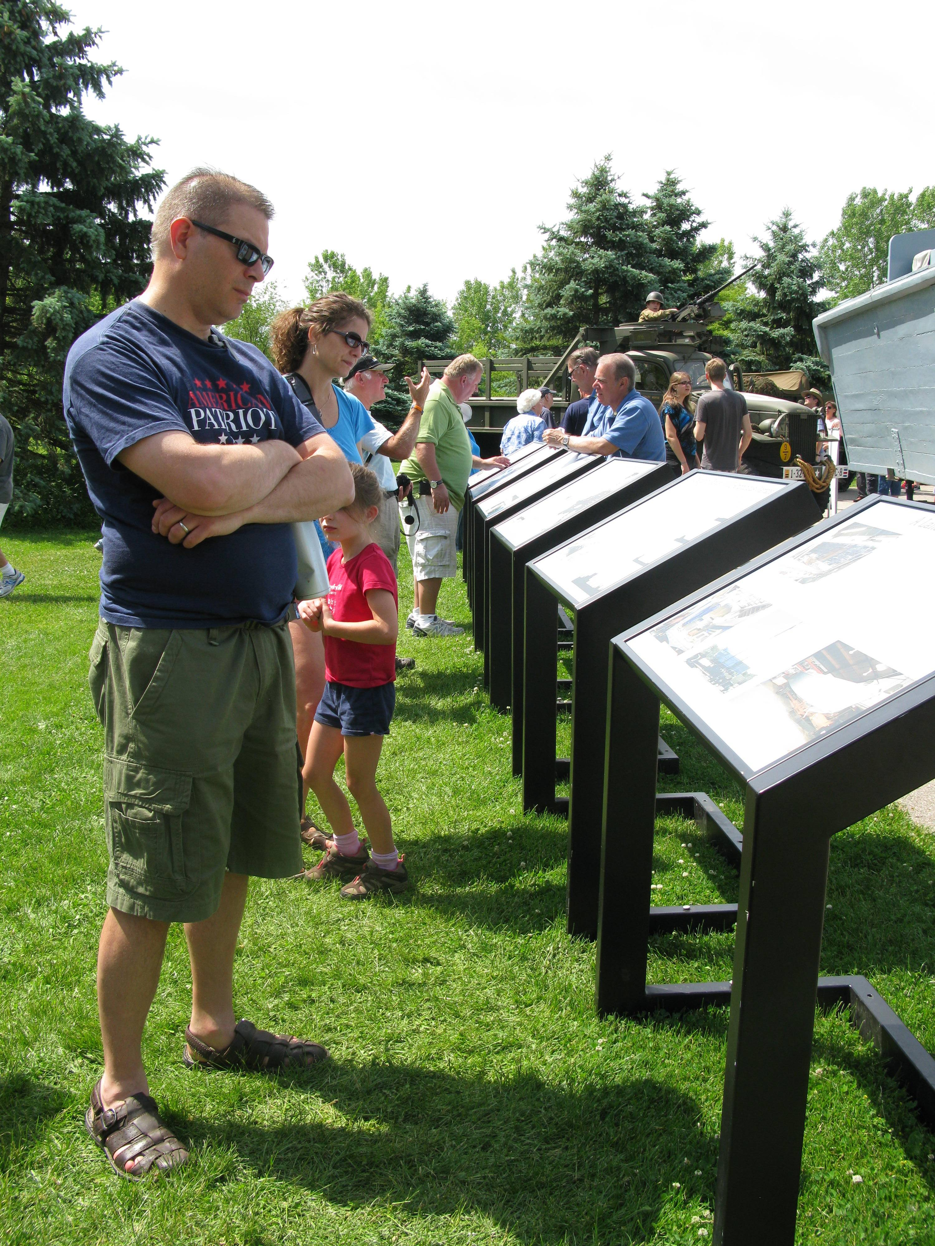 Kevin Oleniczak of Wheaton and wife, Sheryl, in the background, read up on war history Saturday at Cantigny Park in Wheaton. Dozens of visitors, including many World War II veterans, marked the 70th anniversary of D-Day, the Allied invasion of France, Saturday at the park.