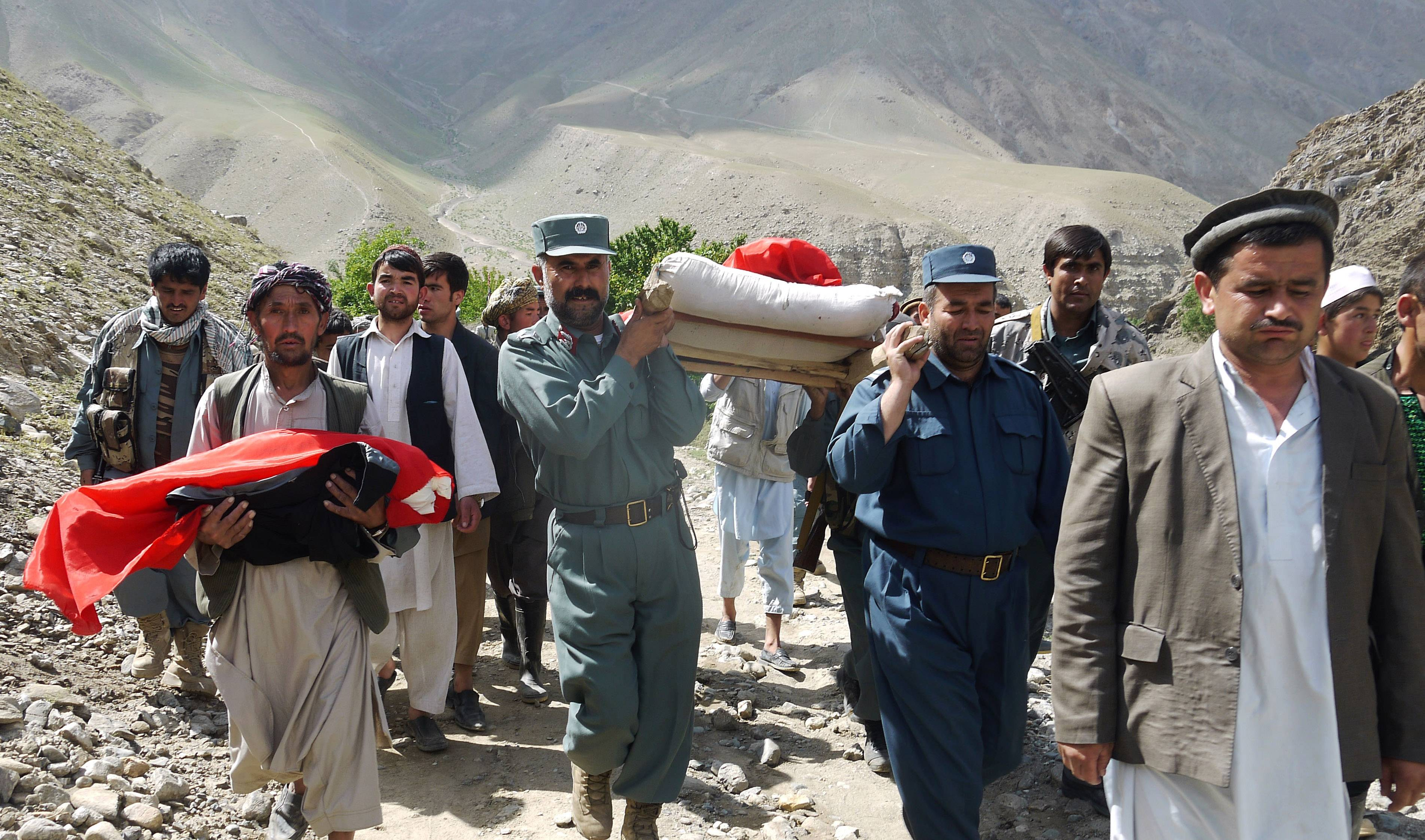 Afghan police and villagers carry bodies of people Saturday after flooding in the northeastern Baghlan province, north of Kabul, Afghanistan.