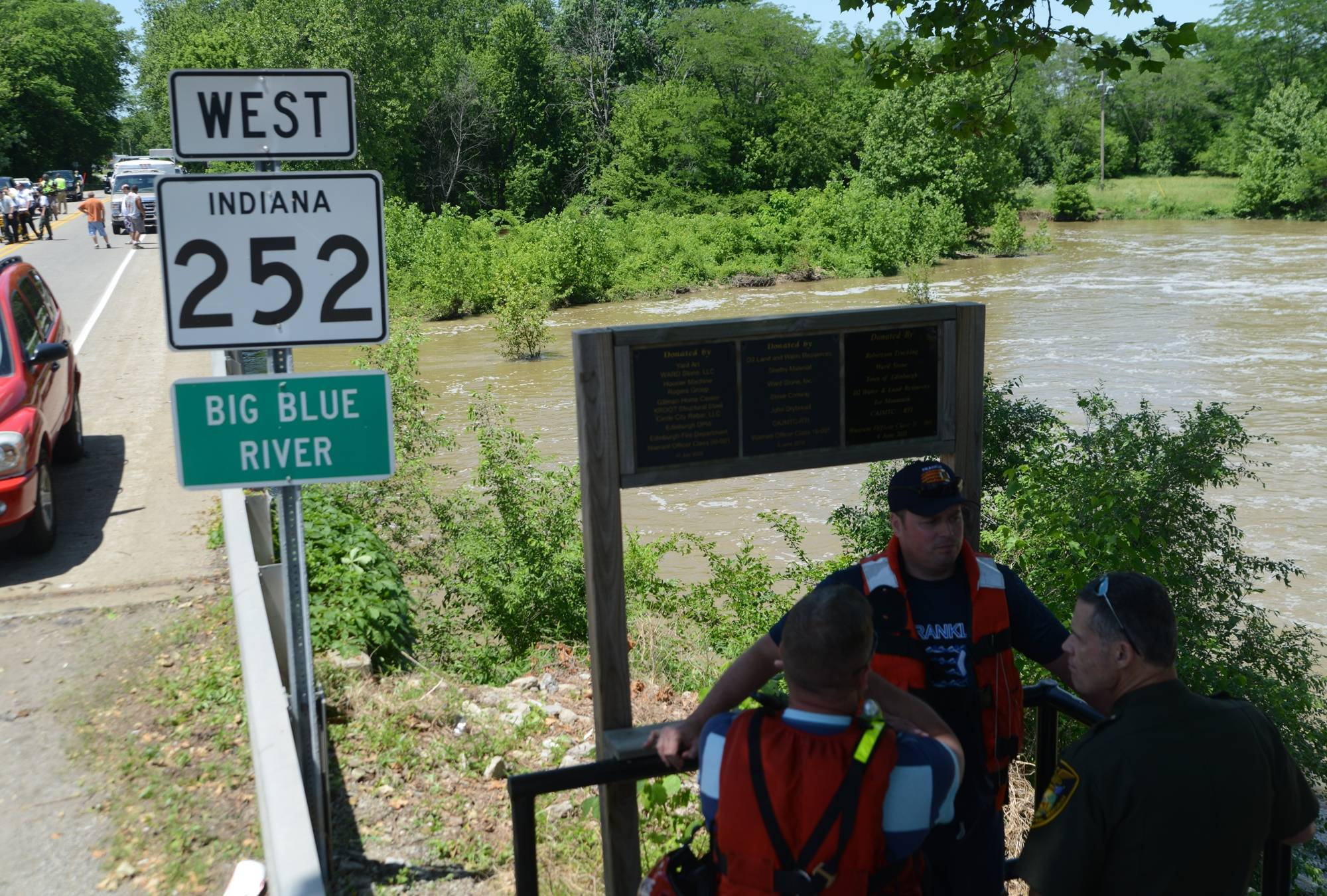 Rescue workers confer Friday on the road above the Big Blue River in Edinburgh, Ind. A teenager was missing and two others were in critical condition after a swimming outing turned tragic.