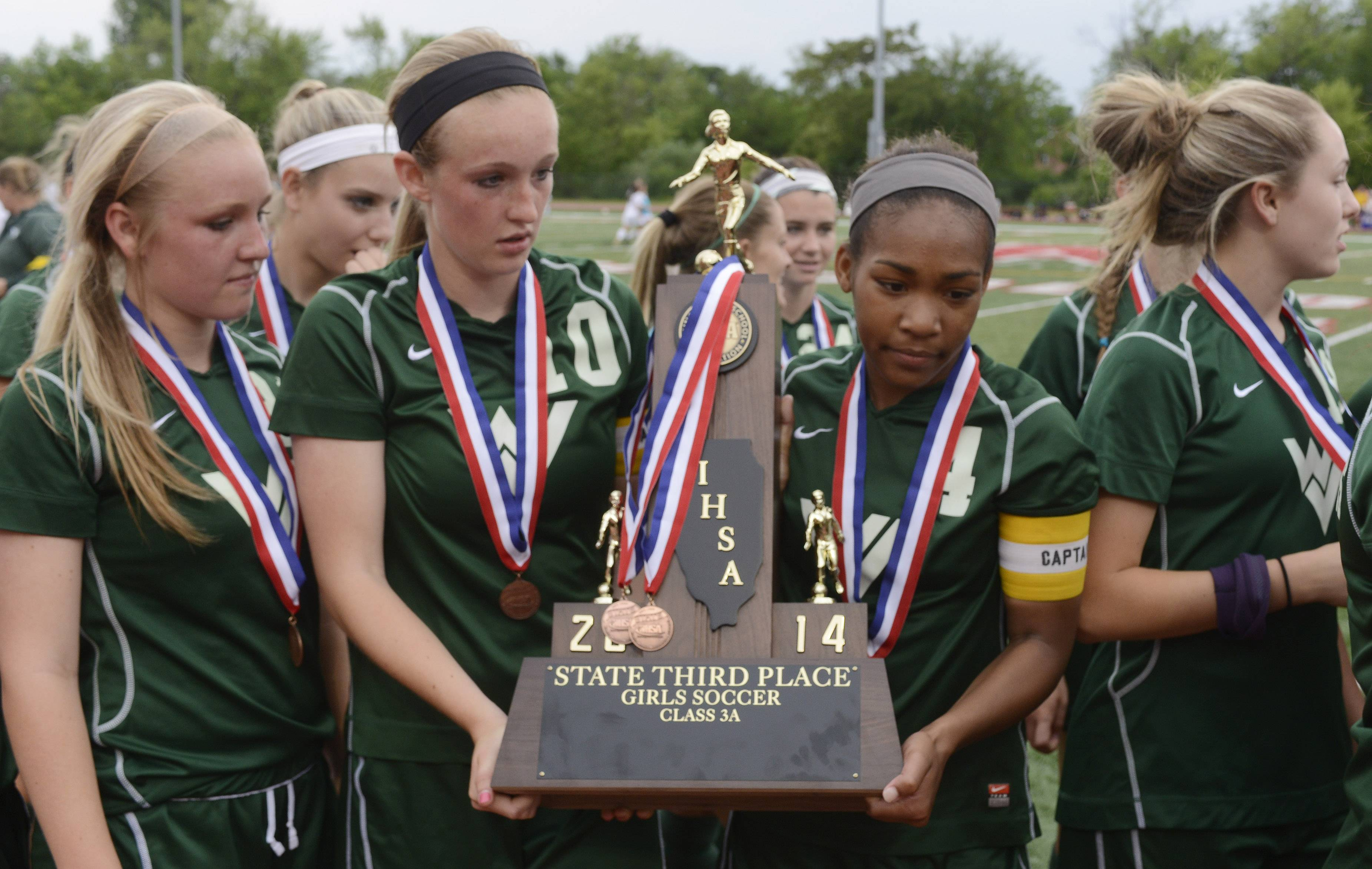 Mackenzie Fuller, left, and Kristen Dodson of Waubonsie Valley hold the third-place girl's soccer trophy after their win over Lincoln-Way North at North Central College in Naperville Saturday.
