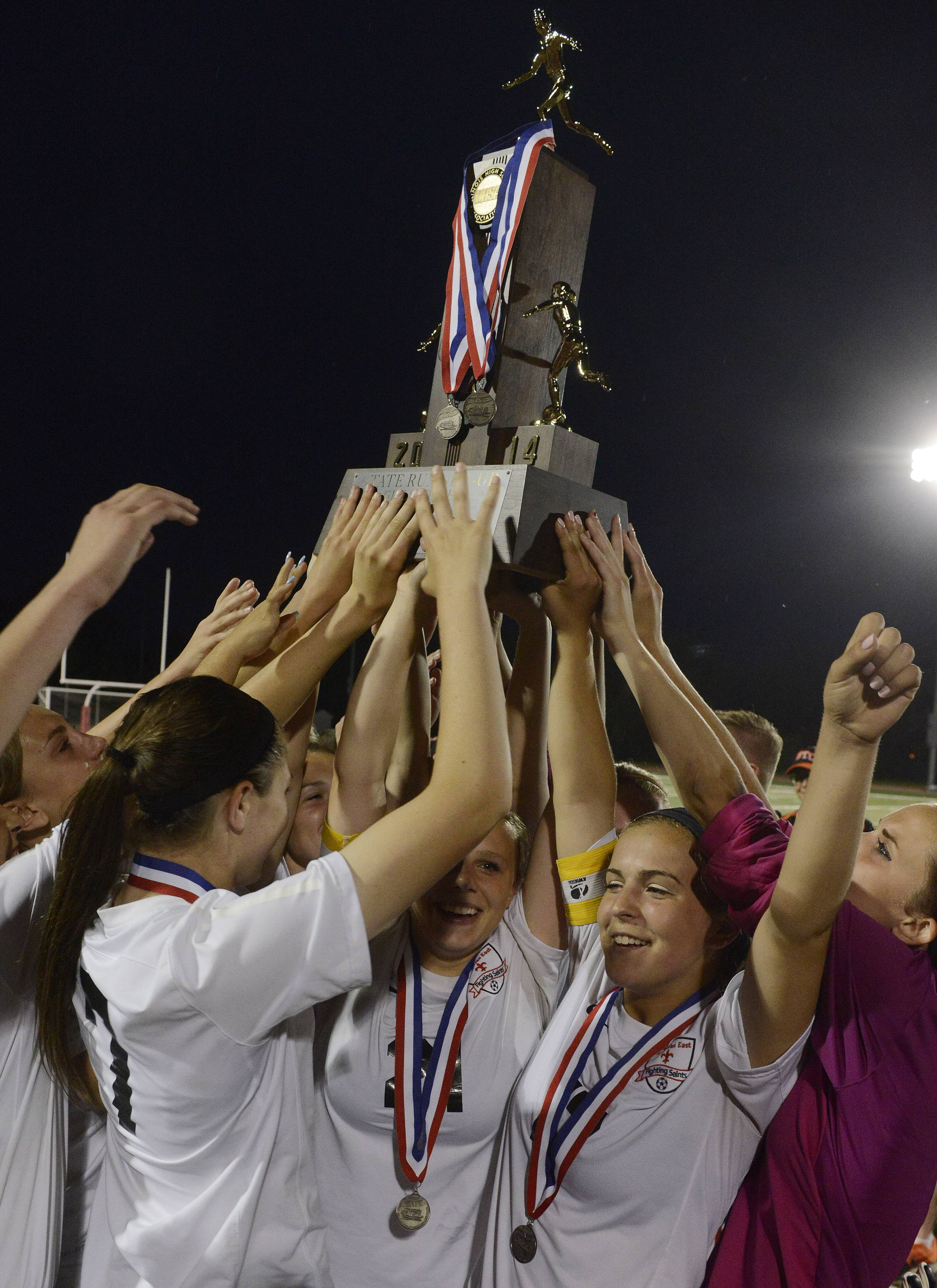 St. Charles East players hold up their second-place trophy after losing 1-0 to New Trier during the girls soccer Class 3A state final at North Central College in Naperville Saturday.