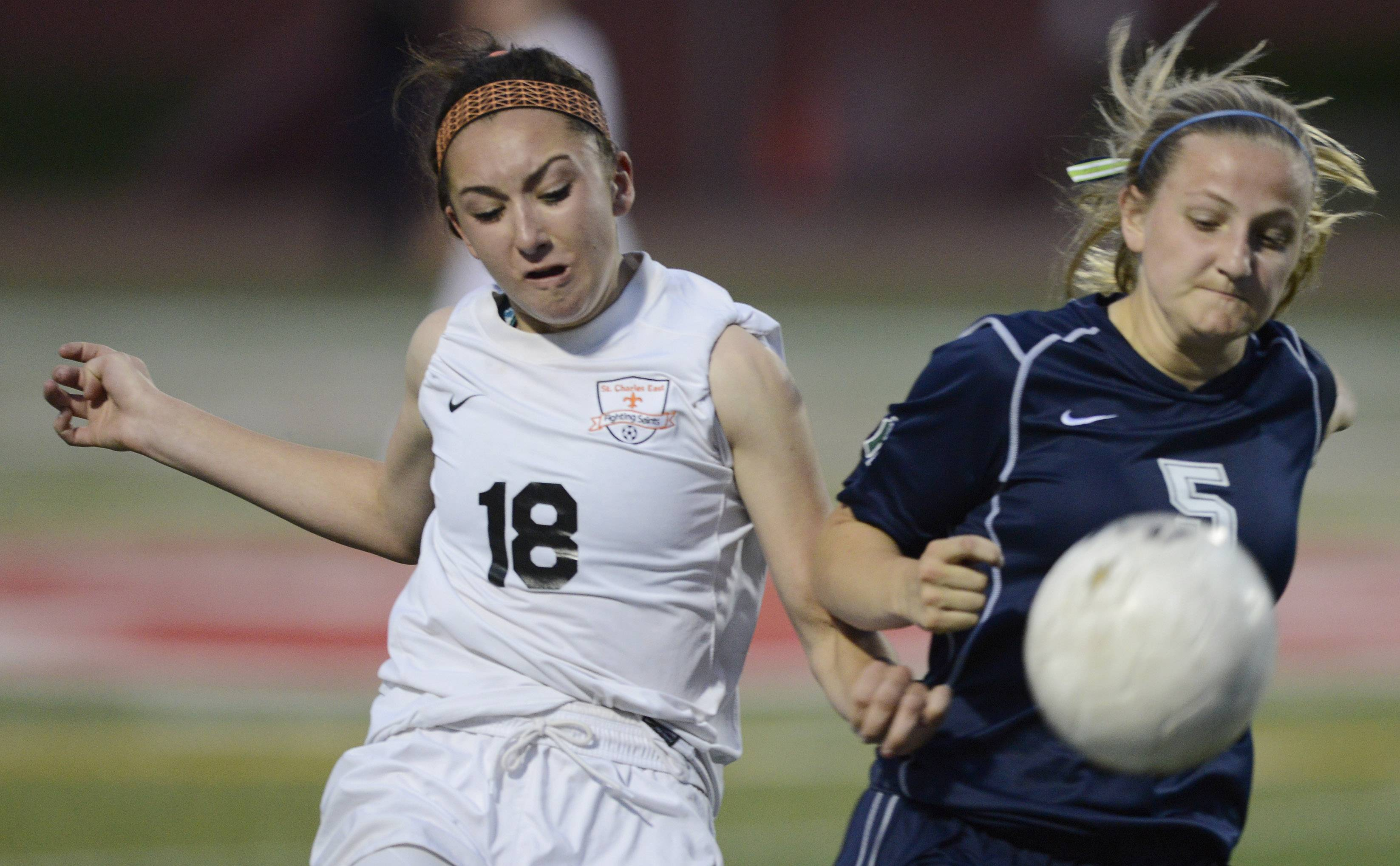 Mallory Moltenhauler, left, of St. Charles East makes contact Maggie Armstrong of New Trier during the girls soccer Class 3A state final at North Central College in Naperville Saturday.
