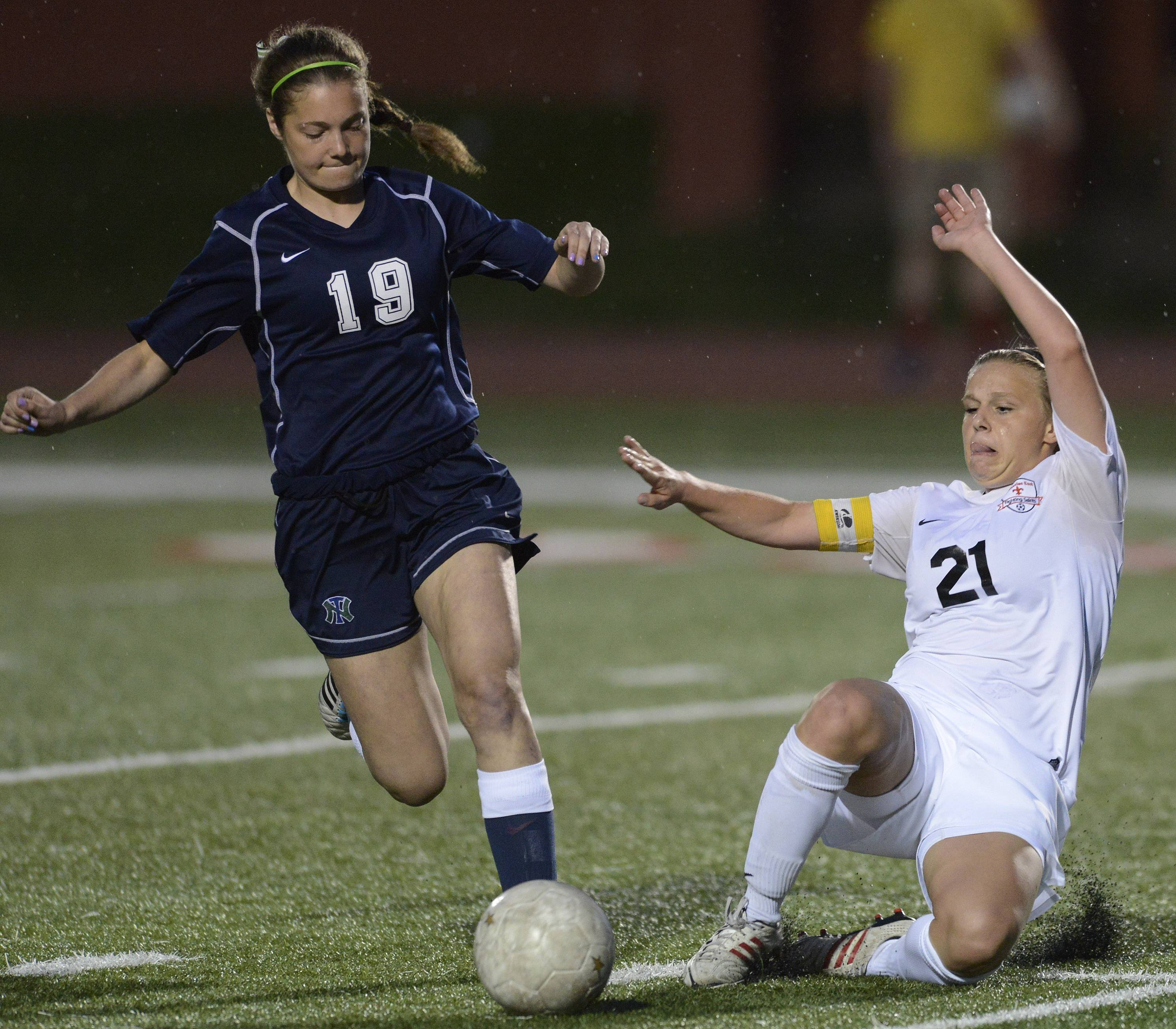 Amanda Hilton, right, of St. Charles East slides past New Trier's Gertie Harris to Maintain possession of the ball during the girls soccer Class 3A state final at North Central College in Naperville Saturday.