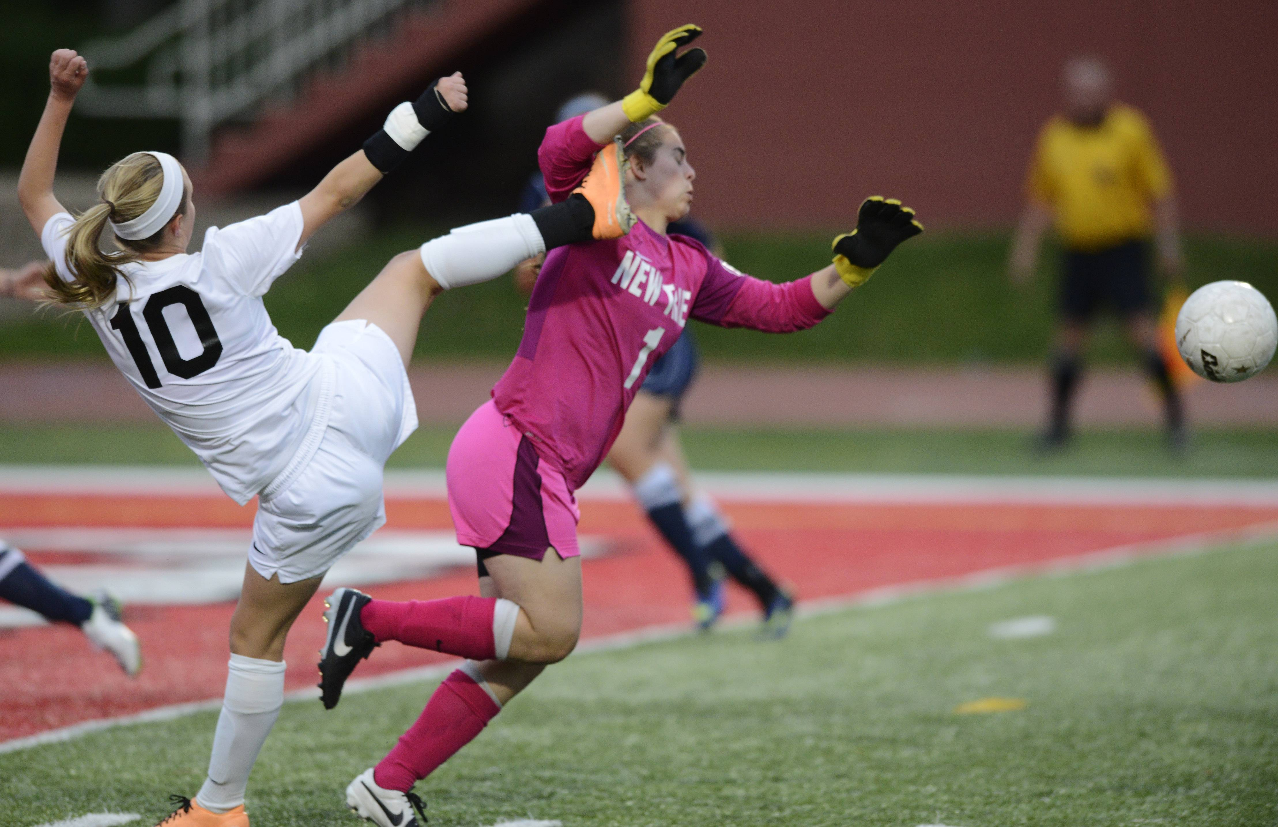 Claire Rasmussen of St. Charles East makes accidental contact with New Trier goal keeper Dani Kaufman on a play in front of the goal during the girls soccer Class 3A state final at North Central College in Naperville Saturday.