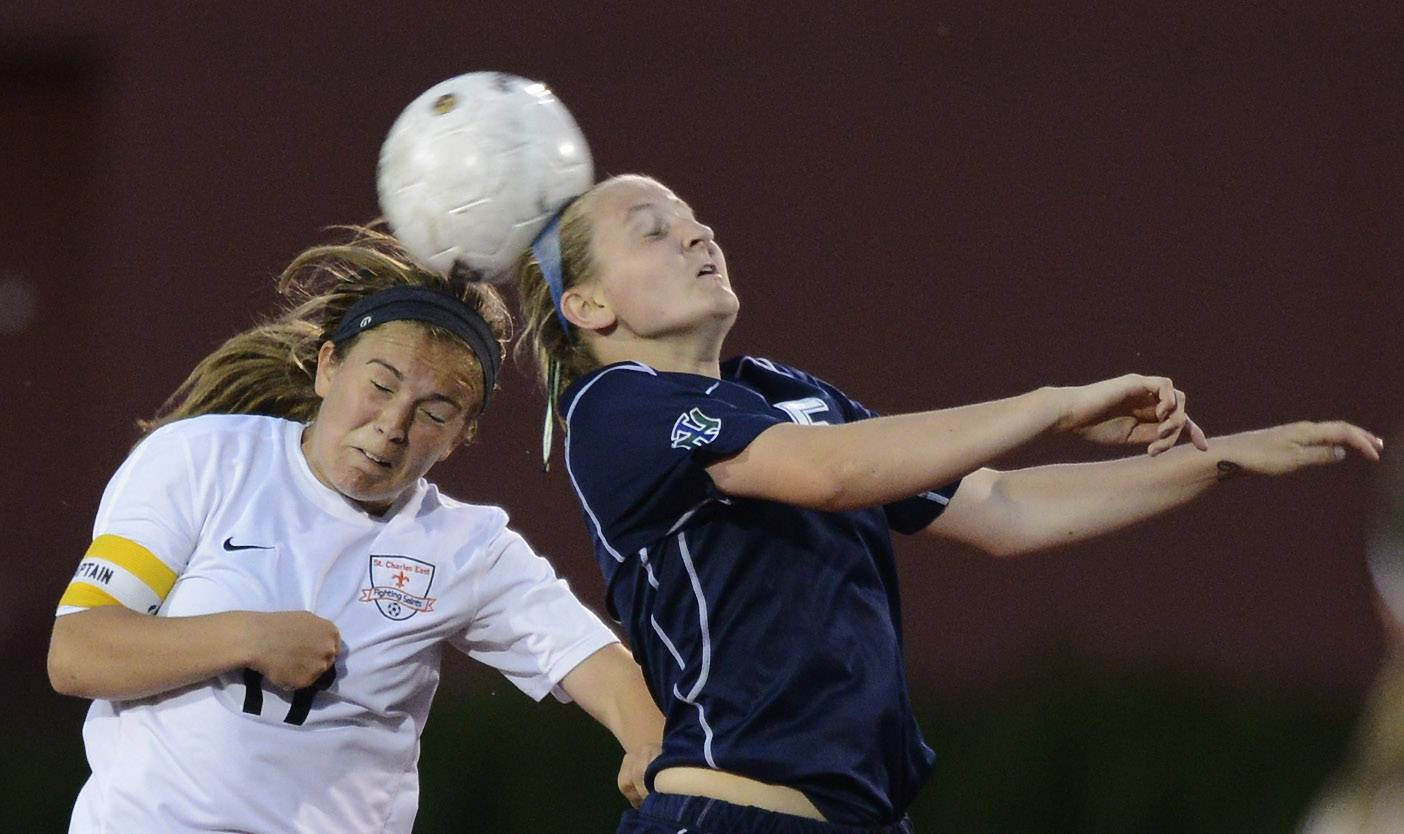 Anna Corirosi, left, of St. Charles East and Maggie Armstrong of New Trier leap for a header during the girls soccer Class 3A state final at North Central College in Naperville Saturday.