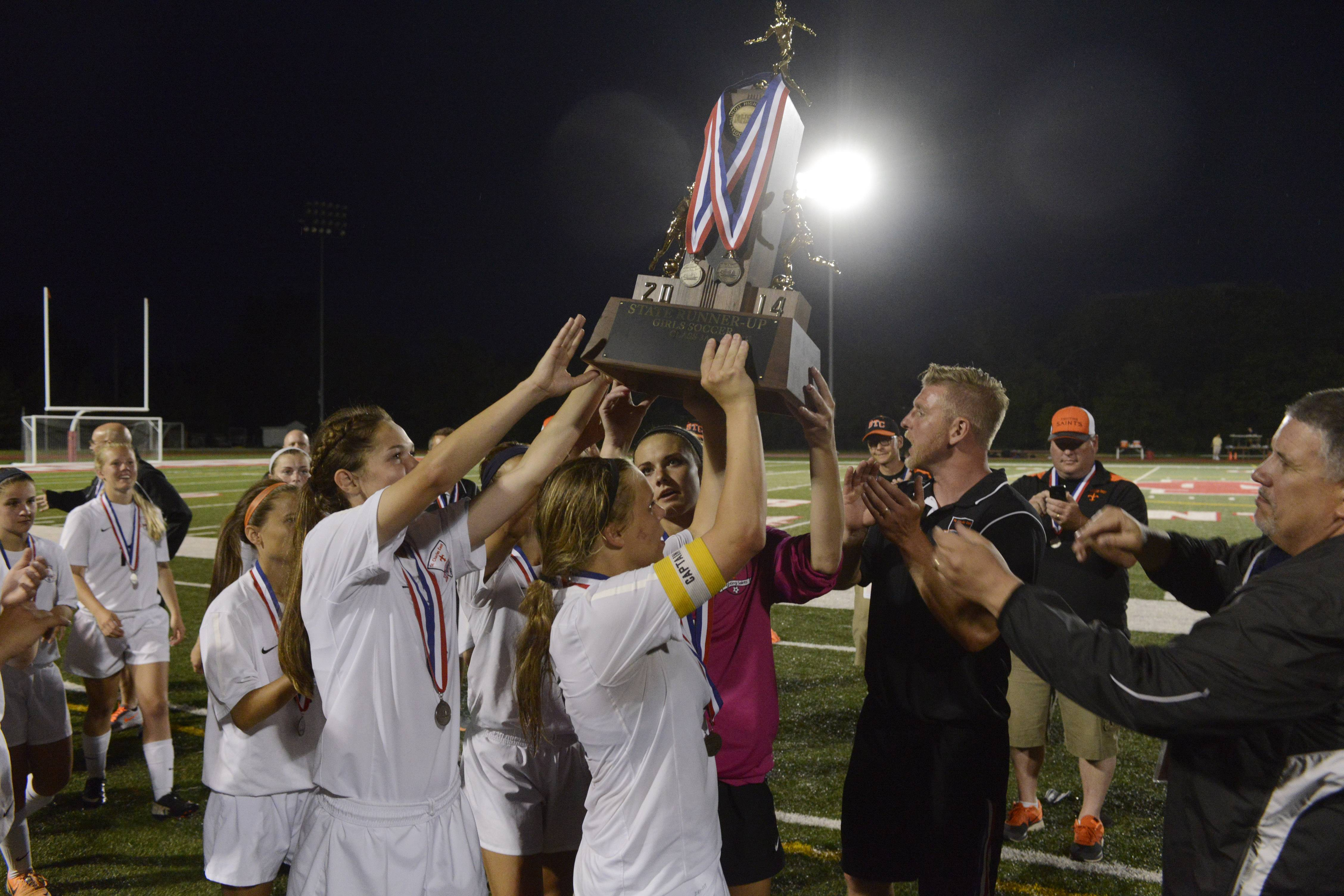 St. Charles East captains accept their team's second place trophy following their 1-0 loss to New Trier during the girls soccer Class 3A state final at North Central College in Naperville Saturday.