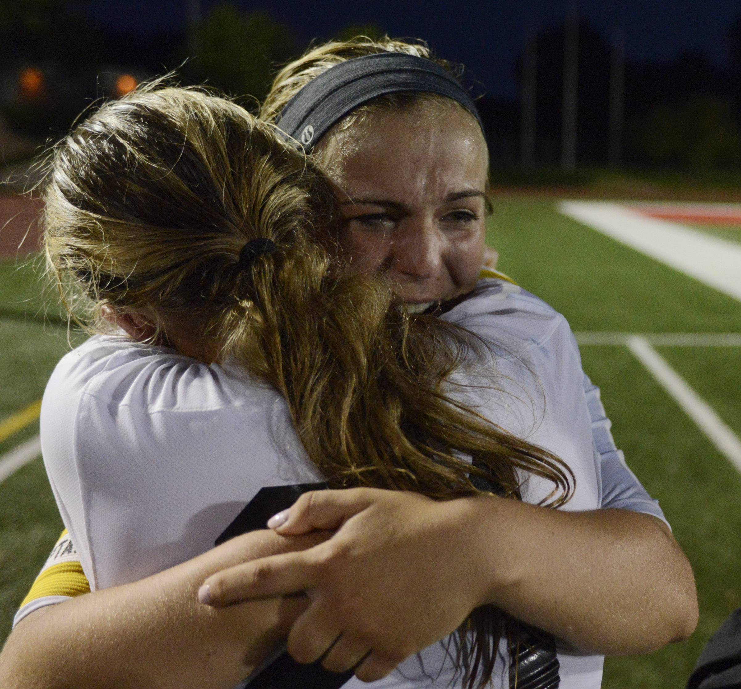 Anna Corirosi, right, of St. Charles East hugs teammate Amanda Hilton following their team's 1-0 loss to New Trier during the girls soccer Class 3A state final at North Central College in Naperville Saturday.