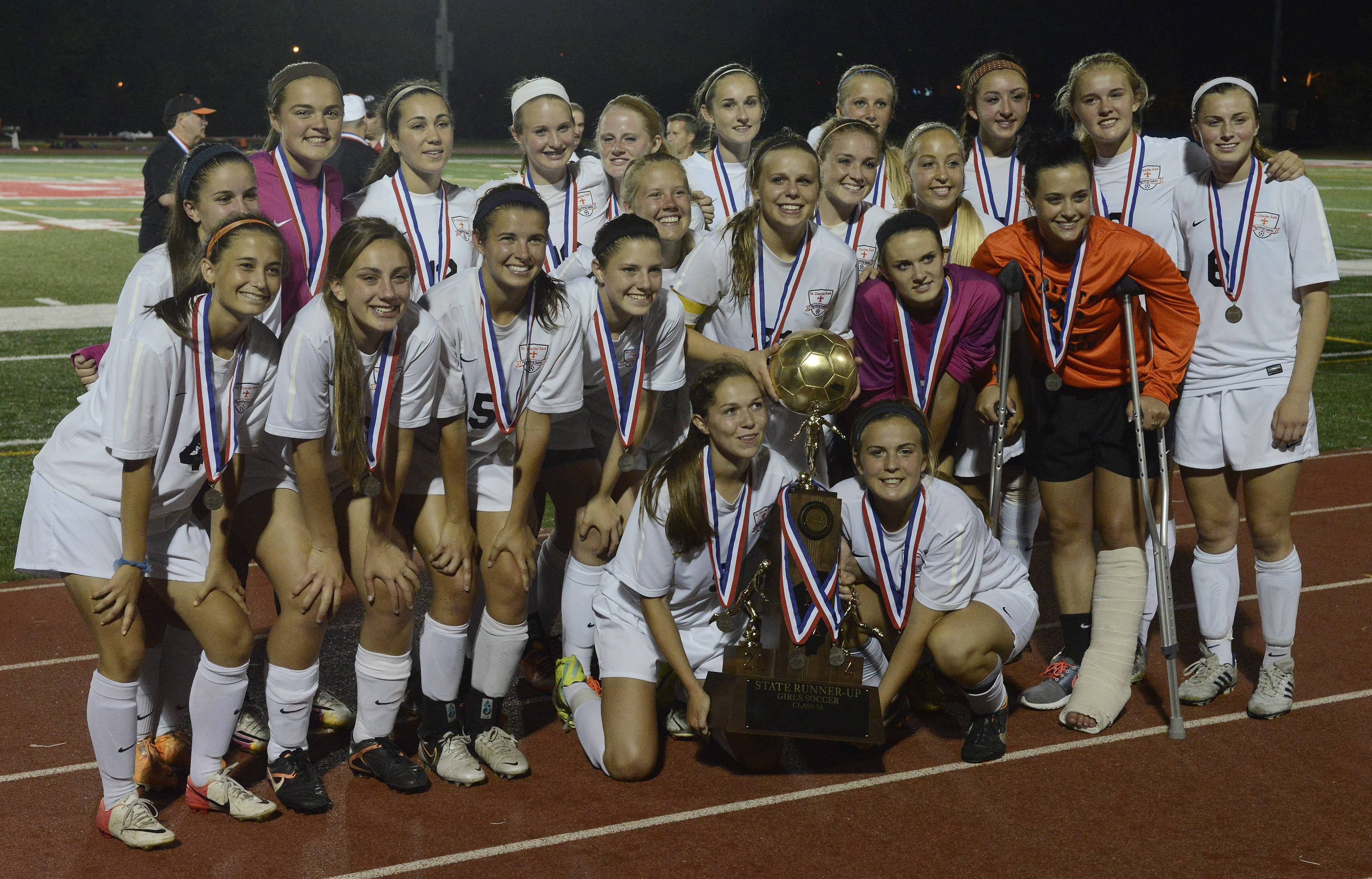 St. Charles East players pose with their second-place trophy following their 1-0 loss to New Trier during the girls soccer Class 3A state final at North Central College in Naperville Saturday.