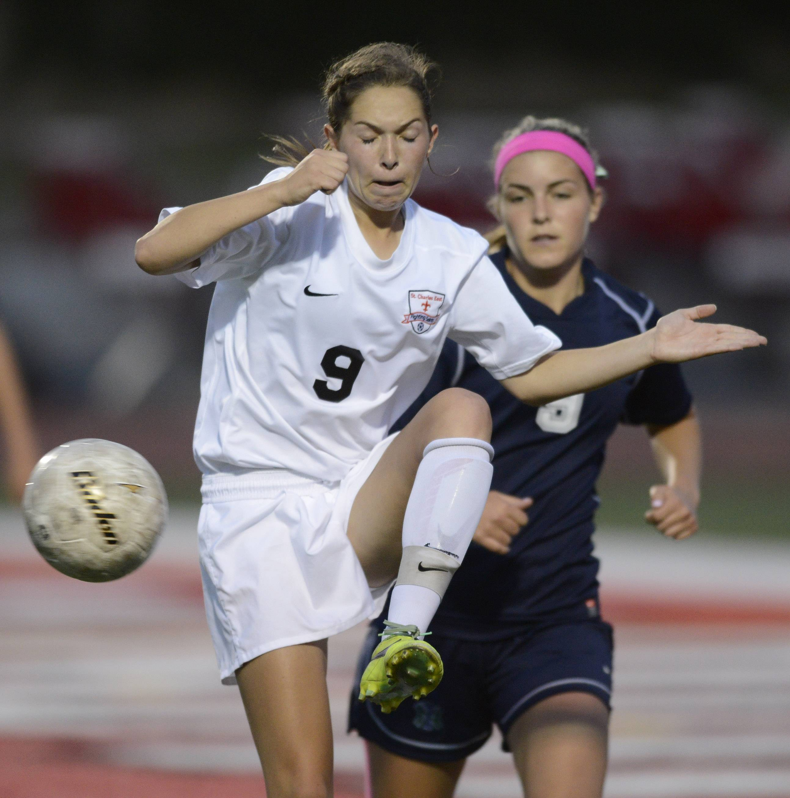 Darcy Cunningham of St. Charles East stretches for the ball in front of Molly Cahill of New Trier during the girls soccer Class 3A state final at North Central College in Naperville Saturday.