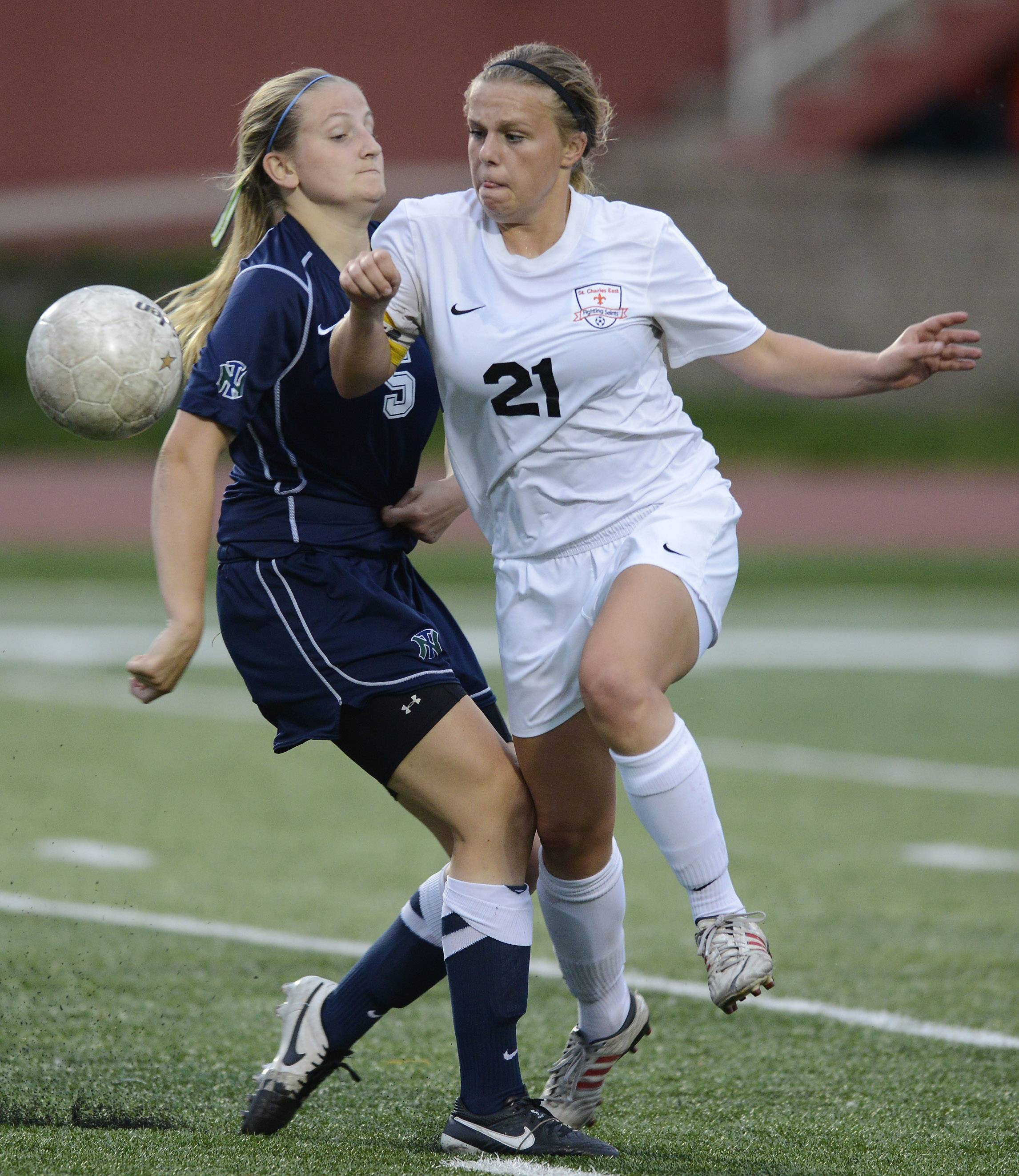 Amanda Hilton, right, of St. Charles East tries to make her way past Maggie Armstrong of New Trier during the girls soccer Class 3A state final at North Central College in Naperville Saturday.