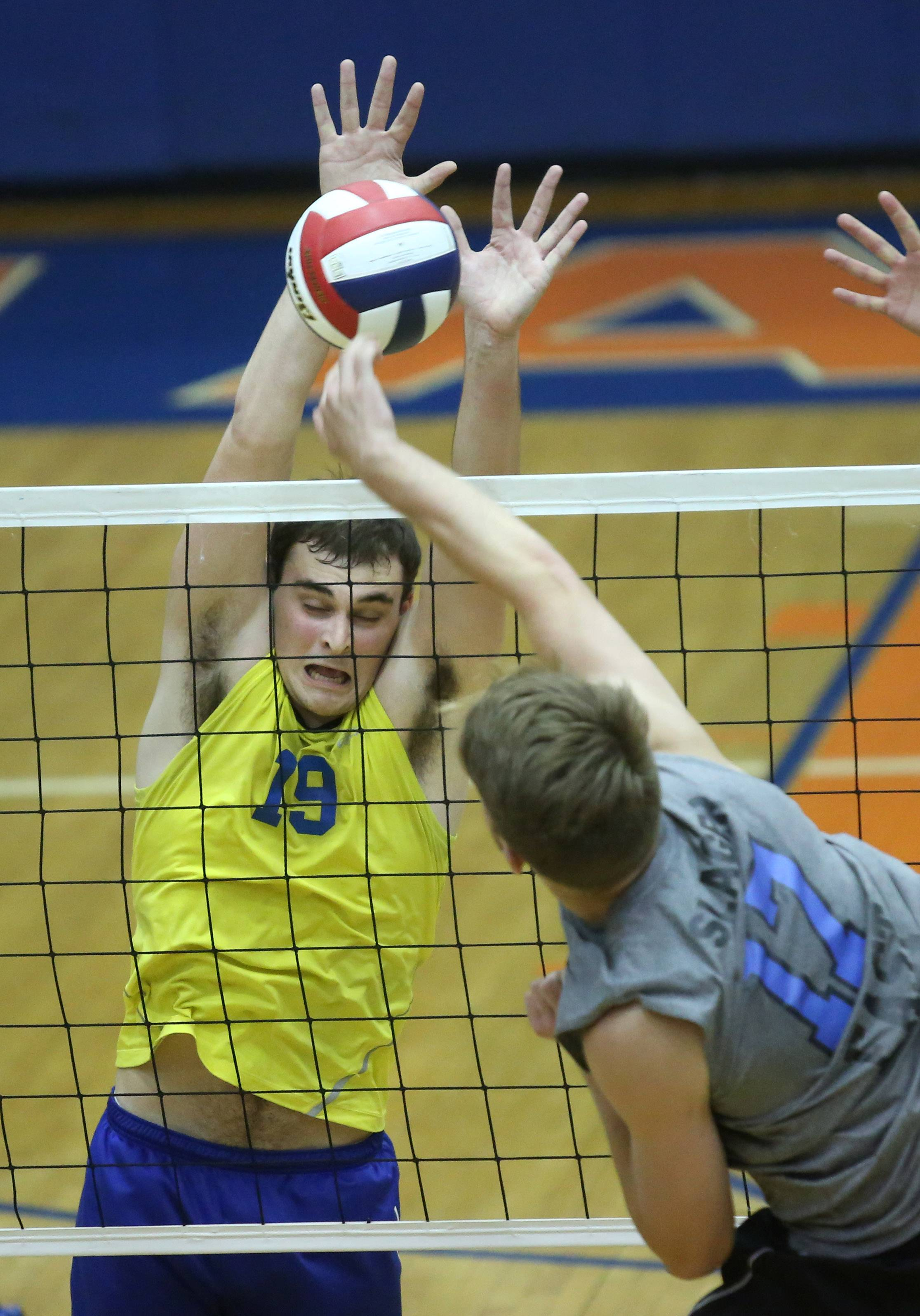 Warren's Max Bongratz blocks a spike by Lincoln-Way East's Carson Slager.