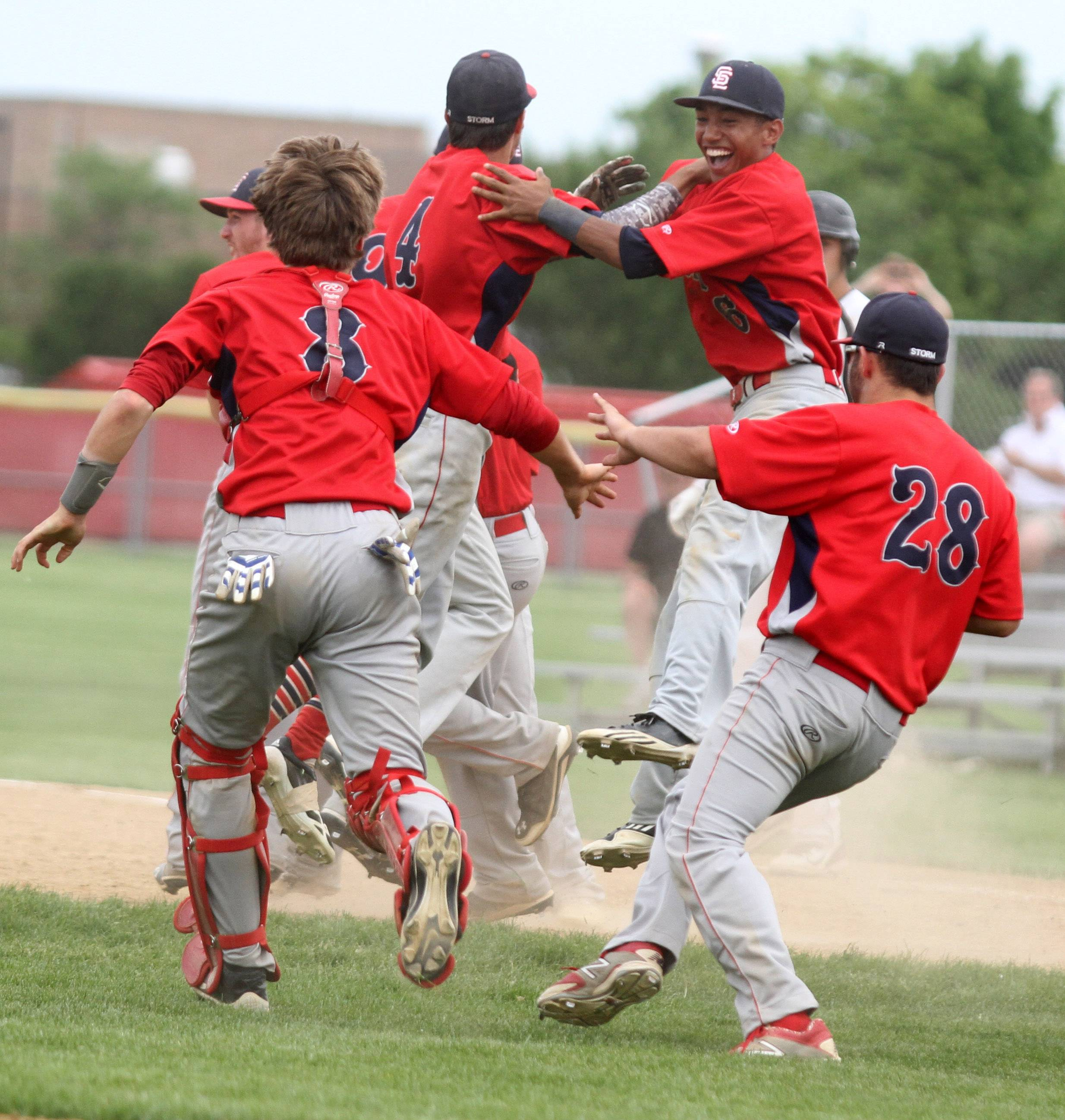 South Elgin catcher Nate Brummel (8) and infielder Antonio Danesi (28) rush the field as South Elgin tops Batavia 8-3 in the Schaumburg sectional championship game Saturday.