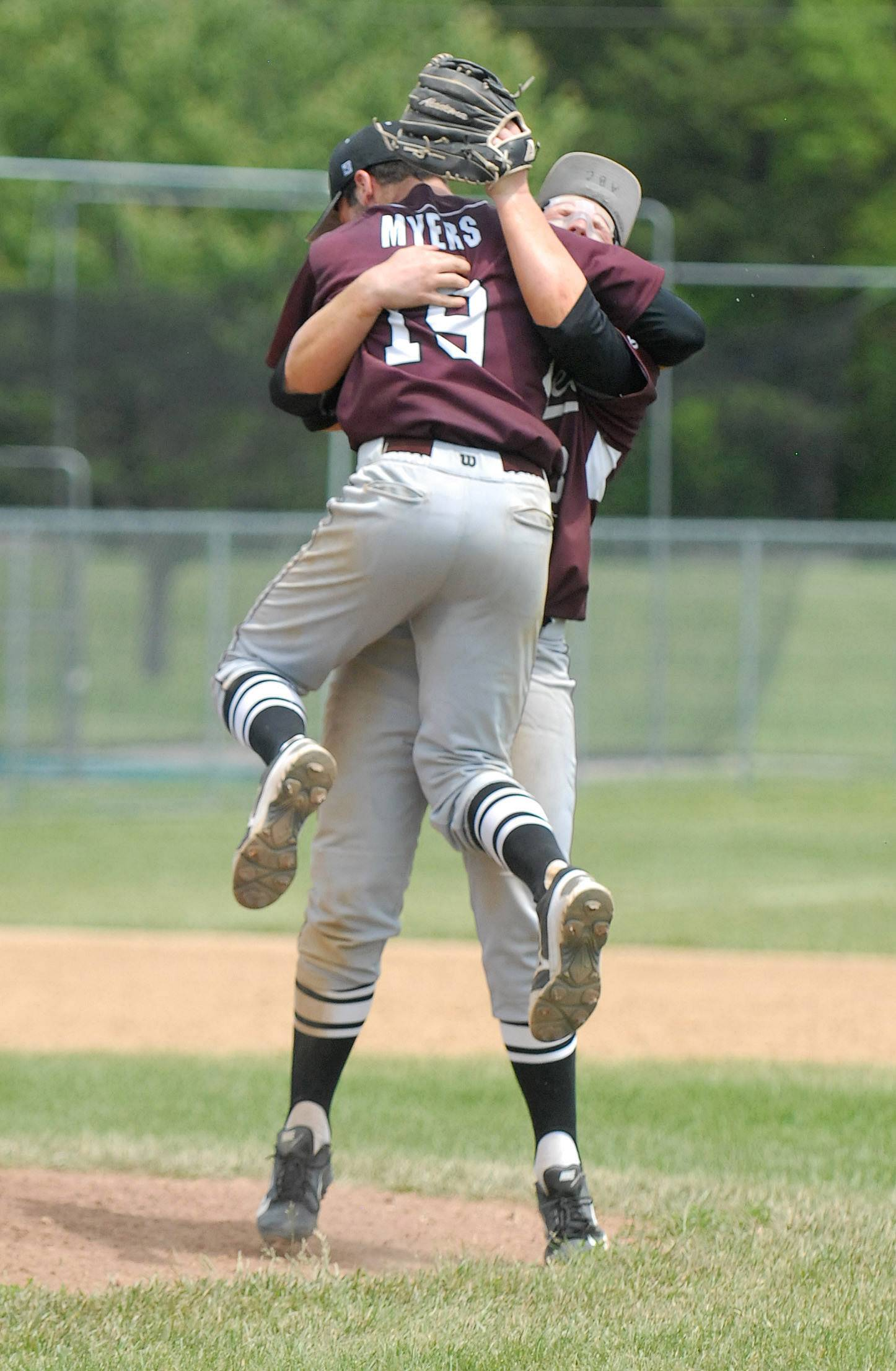 Prairie Ridge's John Myers (19) leaps into the arms of teammate Caleb Aldridge as the Wolves celebrate their Class 4A McHenry sectional championship at Peterson Park on Saturday.