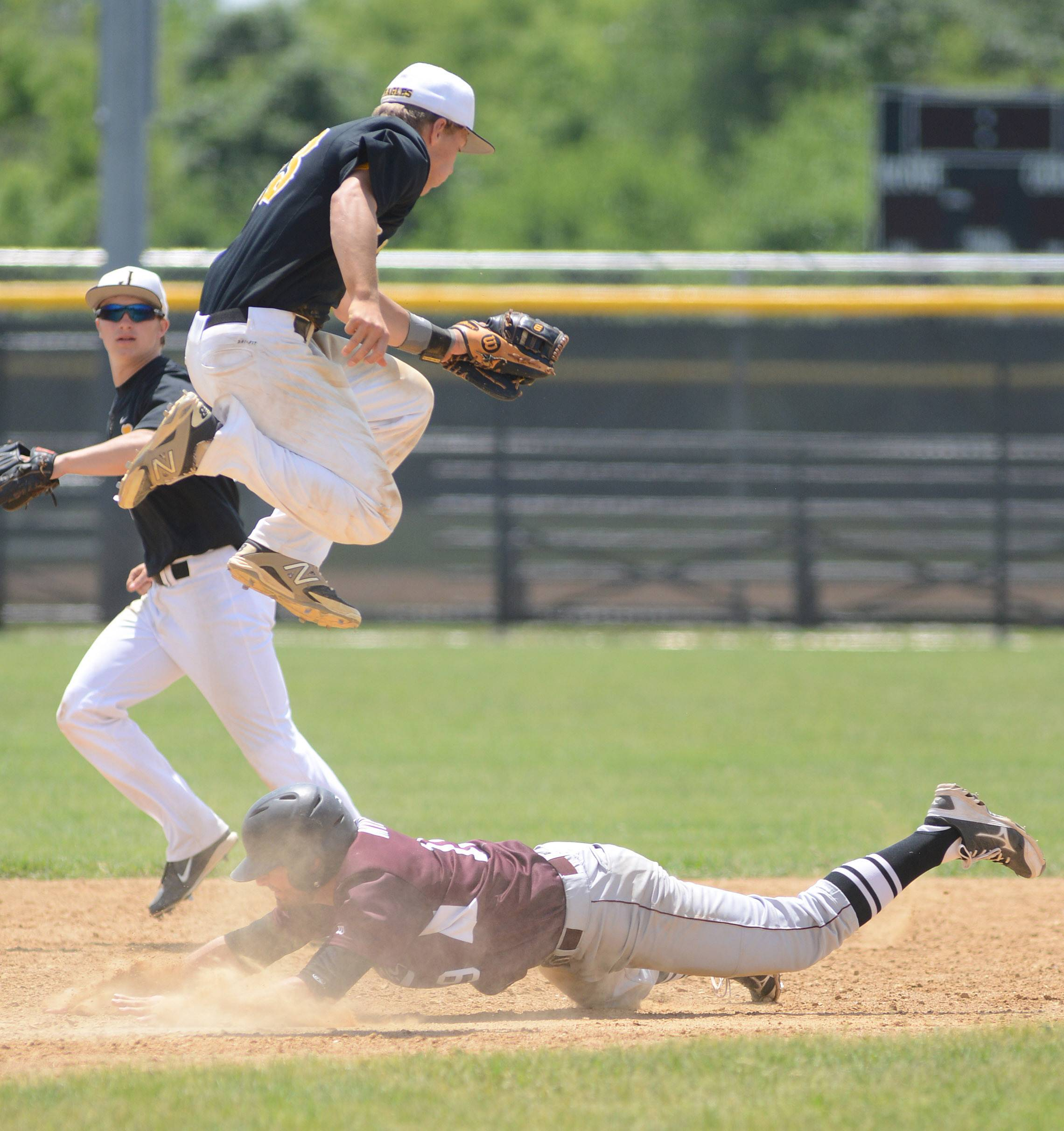 Laura Stoecker/lstoecker@dailyherald.comJacobs' Matt Kozlak leaps to avoid a collision with Prairie Ridge's John Myers as he slides safely into second base in the fifth inning of the Class 4A McHenry sectional championship at Peterson Park on Saturday.