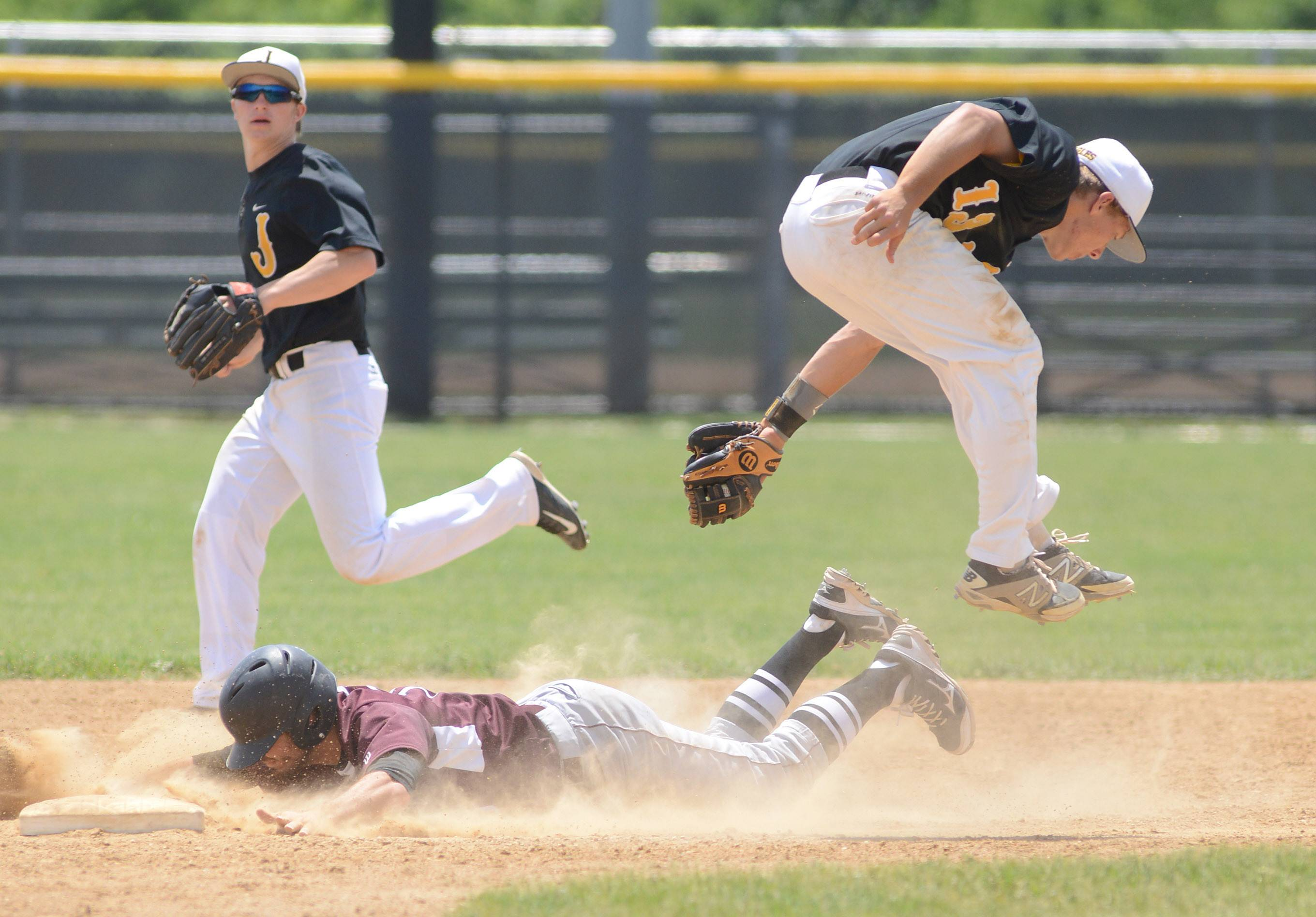 Jacobs' Matt Kozlak leaps to avoid a collision with Prairie Ridge's John Myers as he slides safely into second base in the fifth inning of the Class 4A McHenry sectional championship game at Peterson Park in McHenry on Saturday.