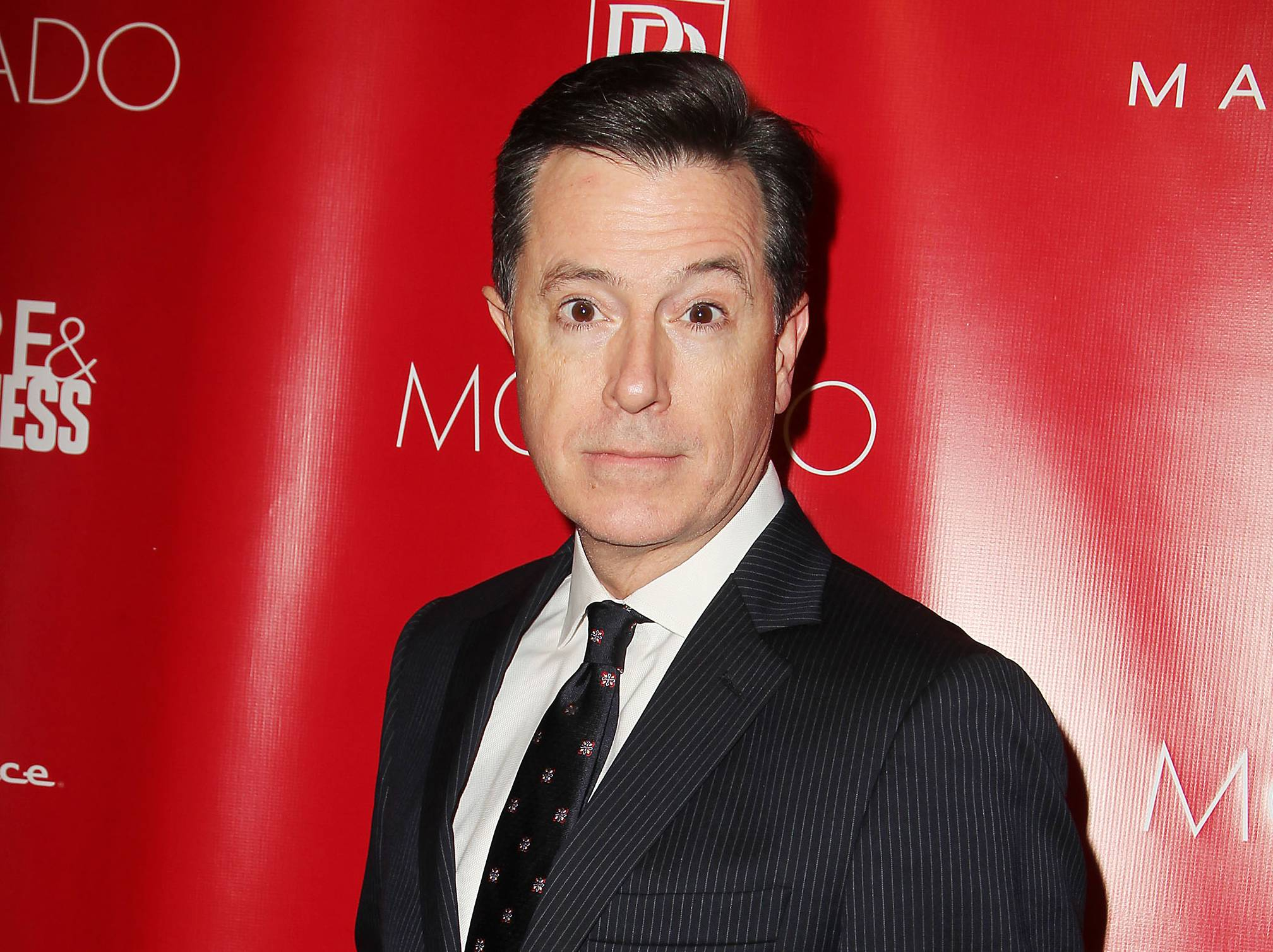 "This Jan. 31, 2014 file image released by Starpix shows Stephen Colbert at the Shape Magazine and Men's Fitness Super Bowl Party in New York. Colbert assailed Amazon.com on his Comedy Central program Wednesday, June 4. Amazon.com is in a contract dispute with Hachette Book Group and has been delaying shipments for some Hachette books, including for Colbert's ""America Again."""
