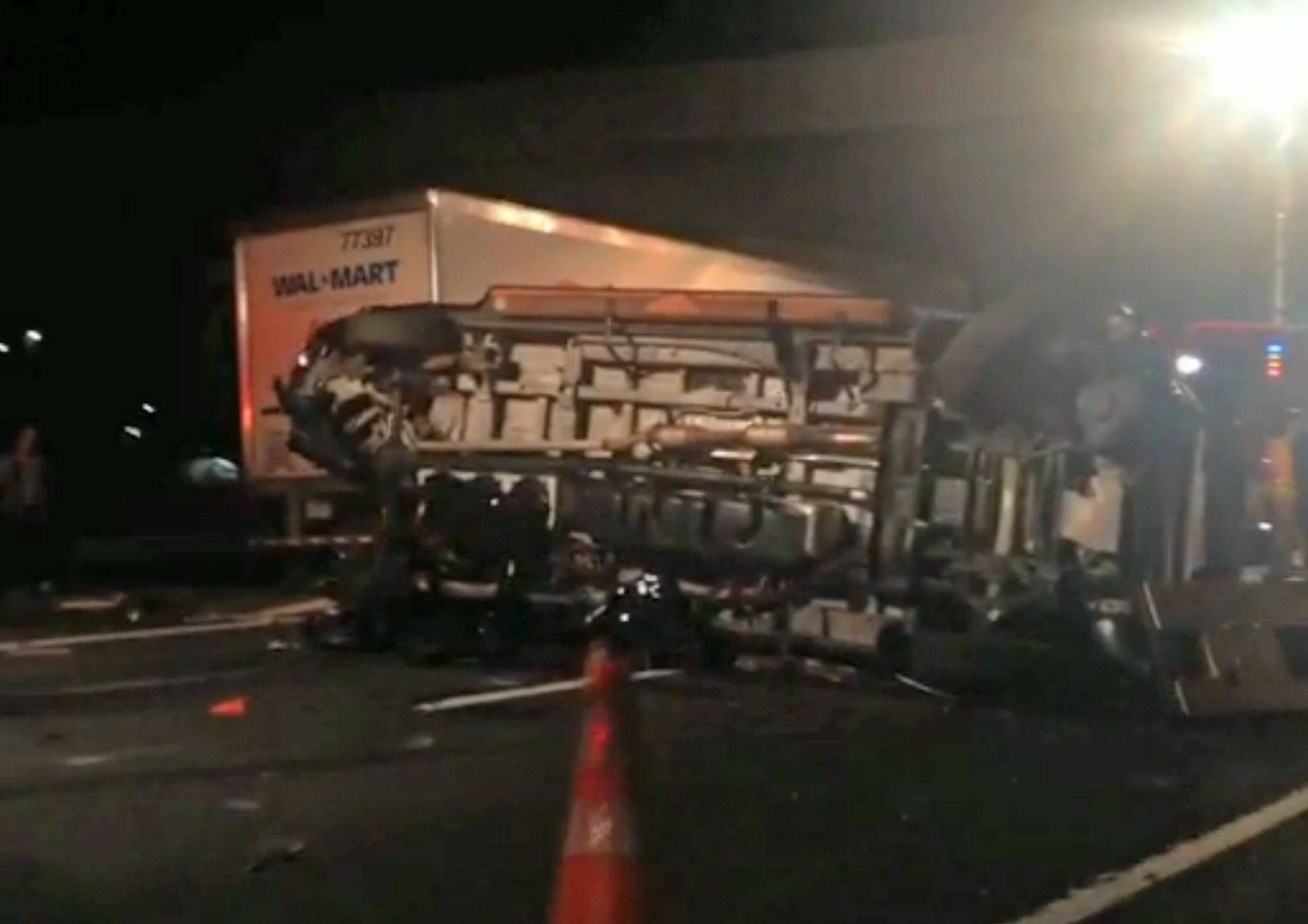 In this image from video the limousine bus carrying Tracy Morgan and six other people lies on it's side early Saturday morning June 7, 2014 on the New Jersey Turnpike. Morgan remained hospitalized as state and federal officials continued their investigation of the six-vehicle crash on the New Jersey Turnpike that took the life of a Morgan friend and left two others seriously injured, authorities say.