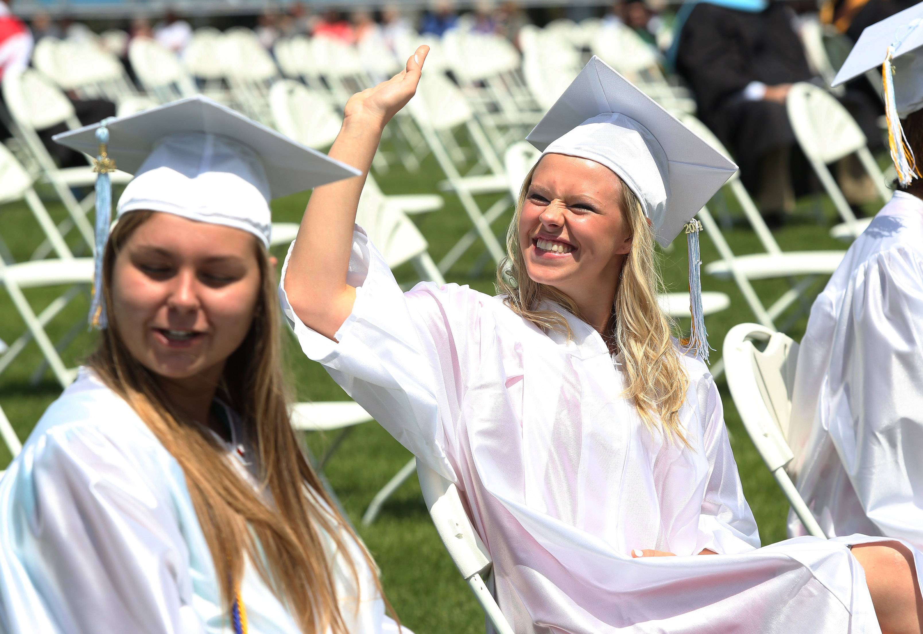 Paulina Kulikowska waves to family during the Maine West High School graduation on Sunday in Des Plaines. Over 500 seniors received their diplomas in the outdoor commencement ceremony.