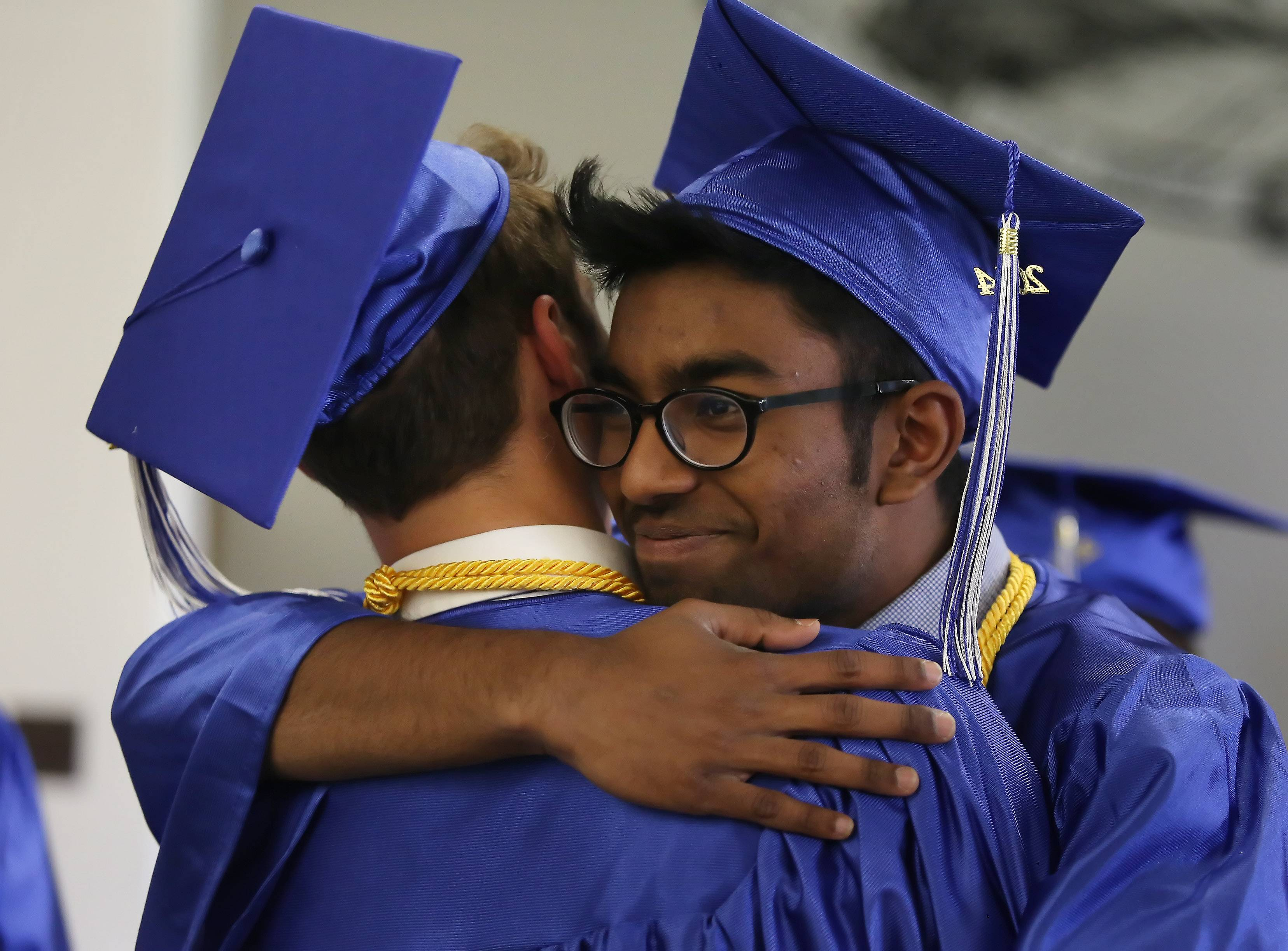 Santhosh Ebenezer, right, hugs classmate David Morrison during the Christian Liberty Academy graduation on Sunday in Arlington Heights. Family and friends watched as 28 seniors received their diplomas in the commencement ceremony.