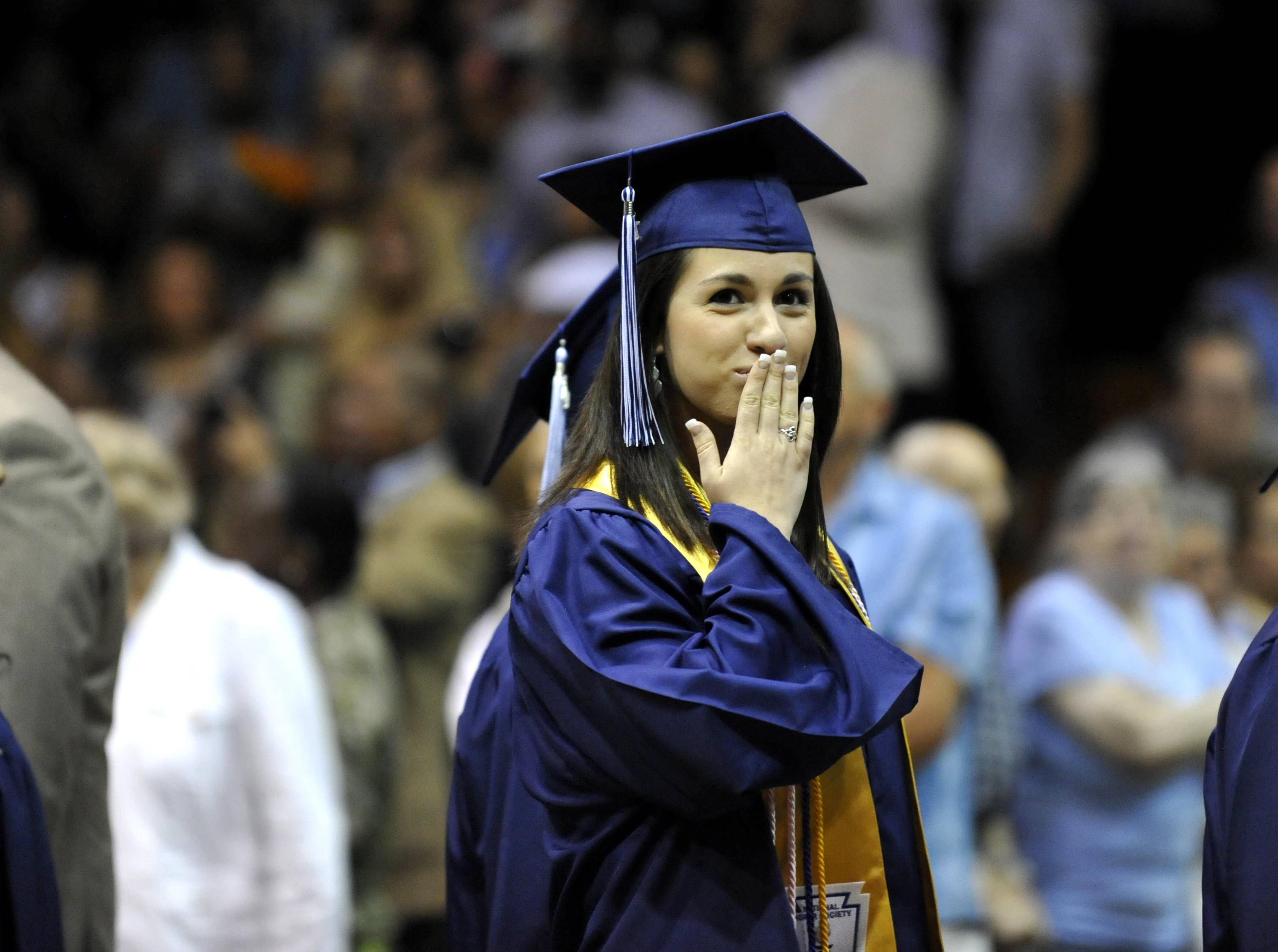 Margaret O'Brien blows a kiss at the start of the Addison Trail High School commencement on Sunday, June 8 at the school.