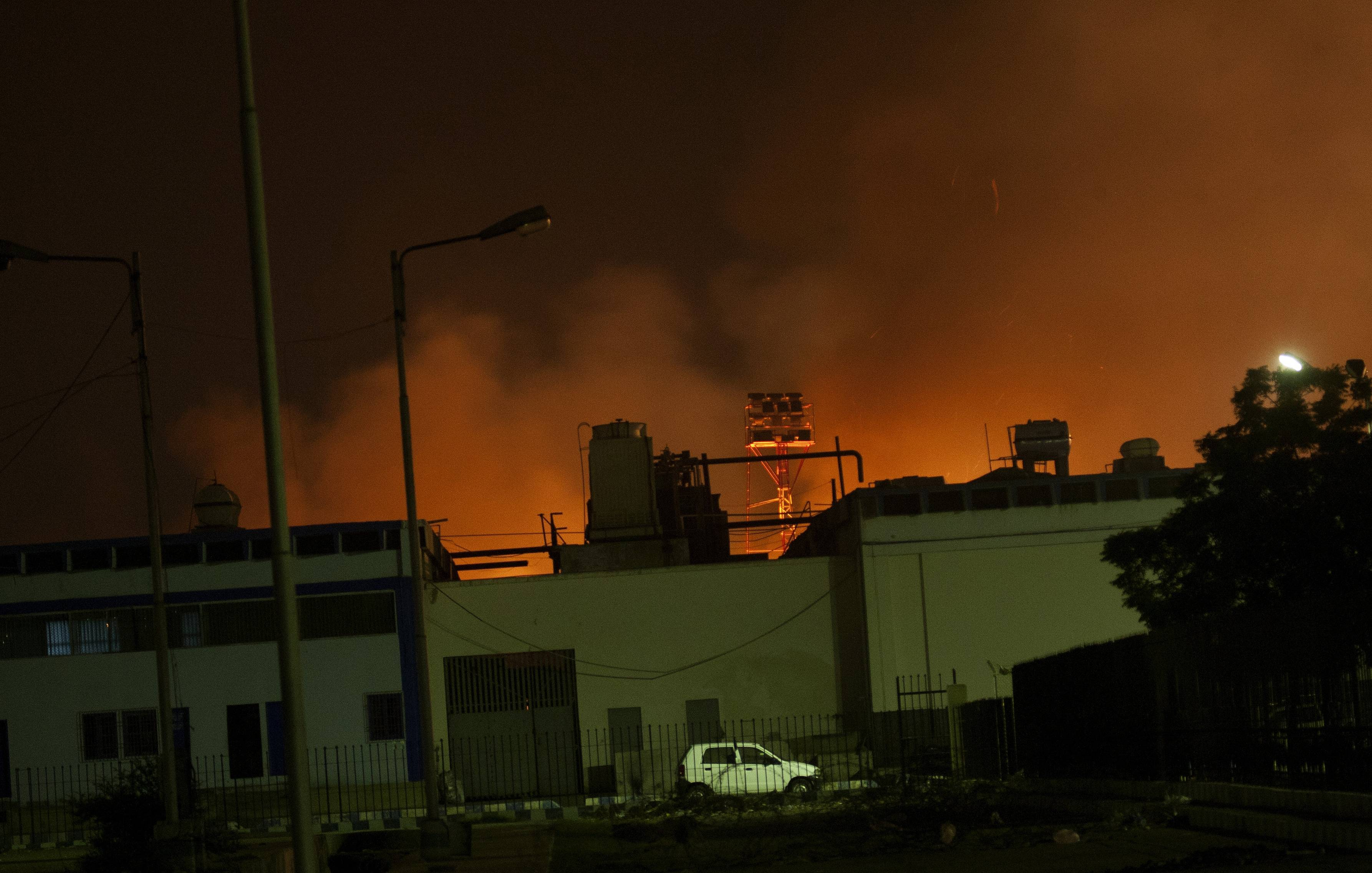 Fire illuminates the sky above Karachi airport terminal where security forces are fighting with attackers Pakistani security troops rushing to Karach on Sunday night in Pakistan. Gunmen stormed an airport terminal used for VIPs and cargo in Pakistan's largest city on Sunday night, killing and wounding scores of people, officials said.