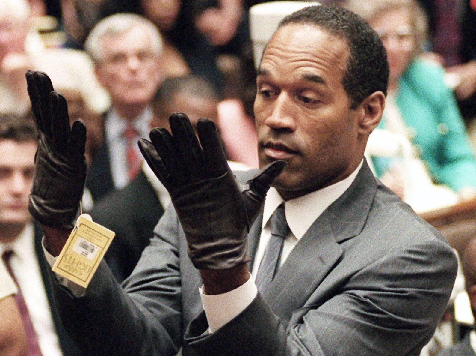 O.J. Simpson holds up his hands before the jury after putting on a new pair of gloves similar to the infamous bloody gloves during his double-murder trial in Los Angeles.