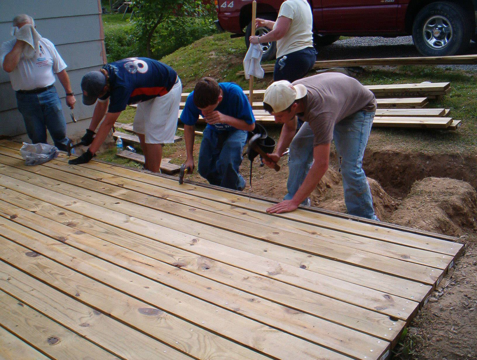 Bob Parks, from left, Andrew Schuetz, Luke Dettlo and Dillon Mugge build a deck for the family of a disabled teen last June in Prestonsburg, Kentucky. High school students from St. Charles Episcopal Church spend a few days each June repairing homes on a mission trip called Mission in the Mountains.