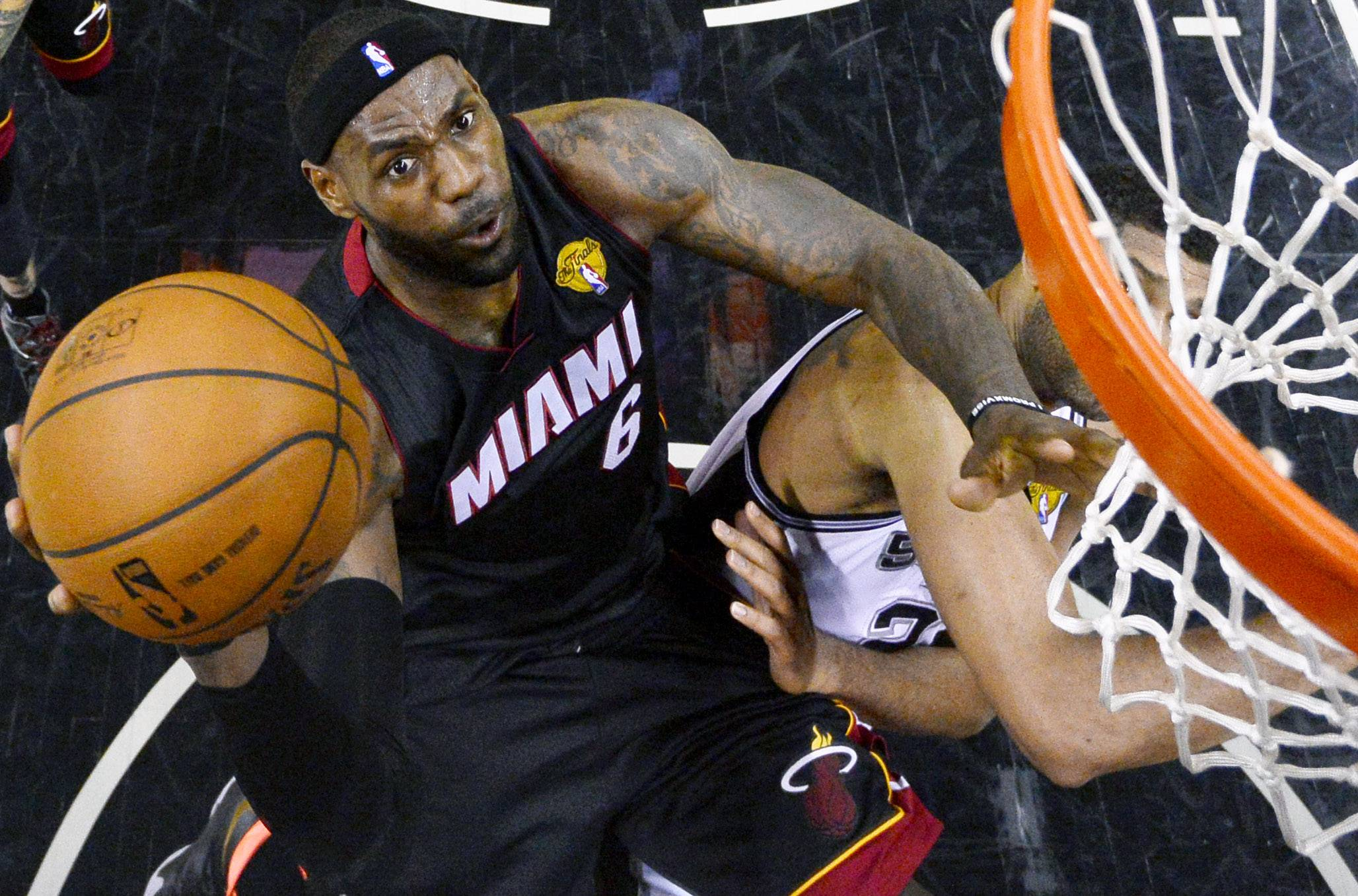 Miami Heat forward LeBron James shoots over San Antonio Spurs forward Tim Duncan (21) during the first half in Game 2 of the NBA basketball finals on Saturday, Nov. 8, 2014, in San Antonio.