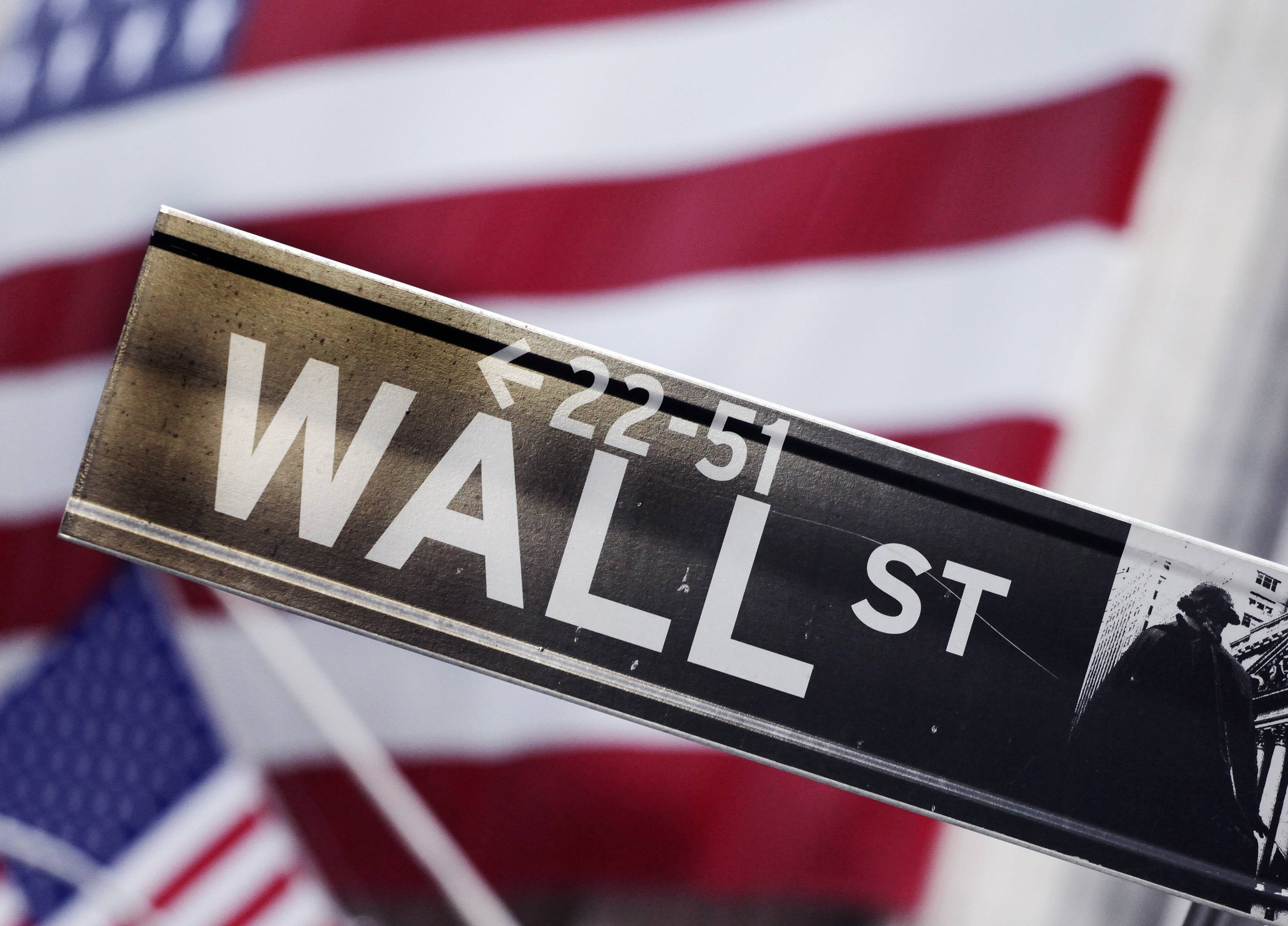 This Aug. 9, 2011 photo shows a Wall Street street sign near the New York Stock Exchange, in New York. U.S. stock futures are heading lower in early trading Tuesday, June 3, 2014, a day after major indexes reached new highs.