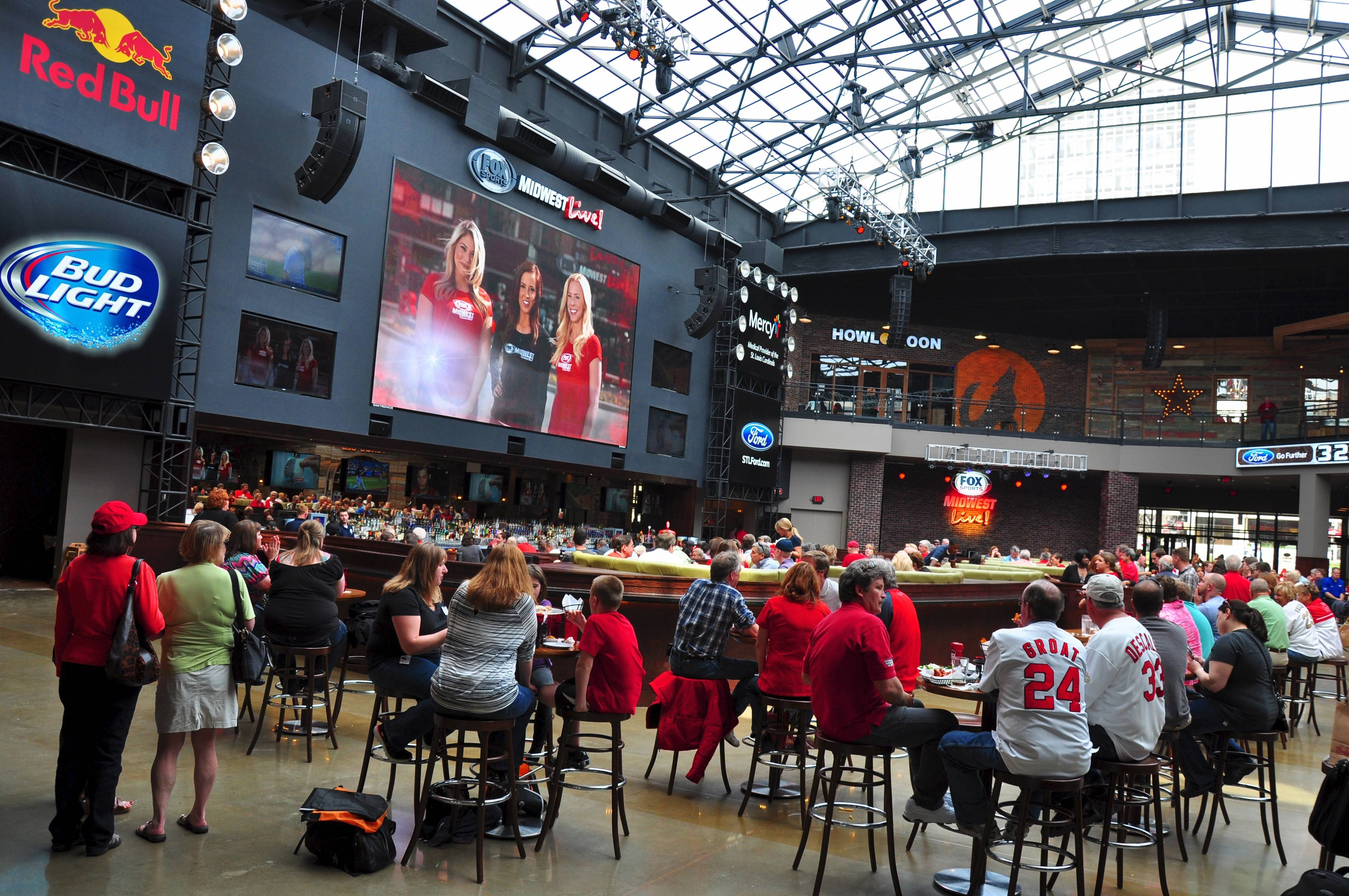 The atrium inside Ballpark Village is covered by a retractable glass roof. Fans can watch sporting events on a giant video screen while enjoying food and drink in climate-controlled comfort.