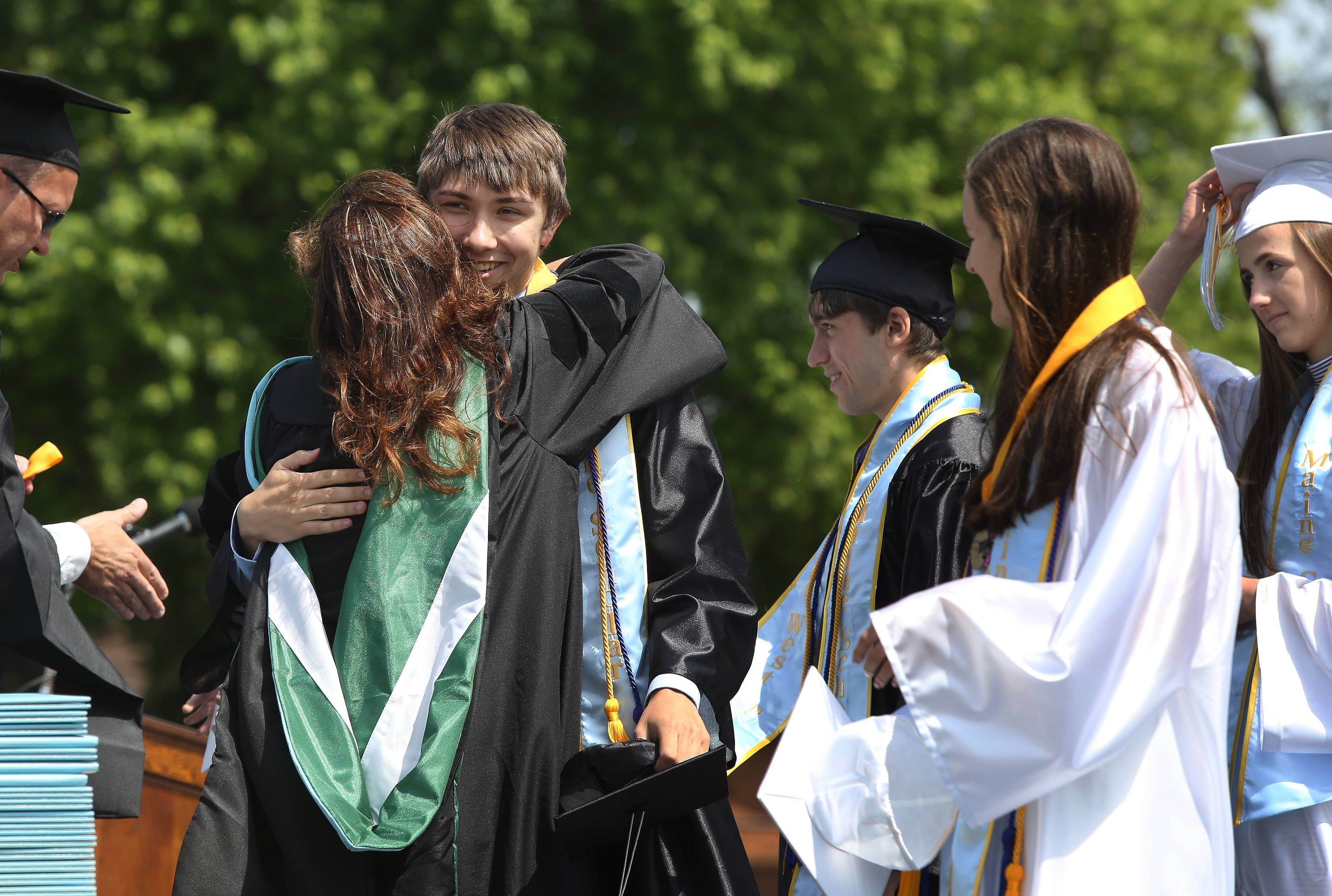 Maine Scholar Eric Etzwiler is hugged by Principal Audrey Haugan as the top 1% were honored during the Maine West High School graduation on Sunday in Des Plaines. Over 500 seniors received their diplomas in the outdoor commencement ceremony.