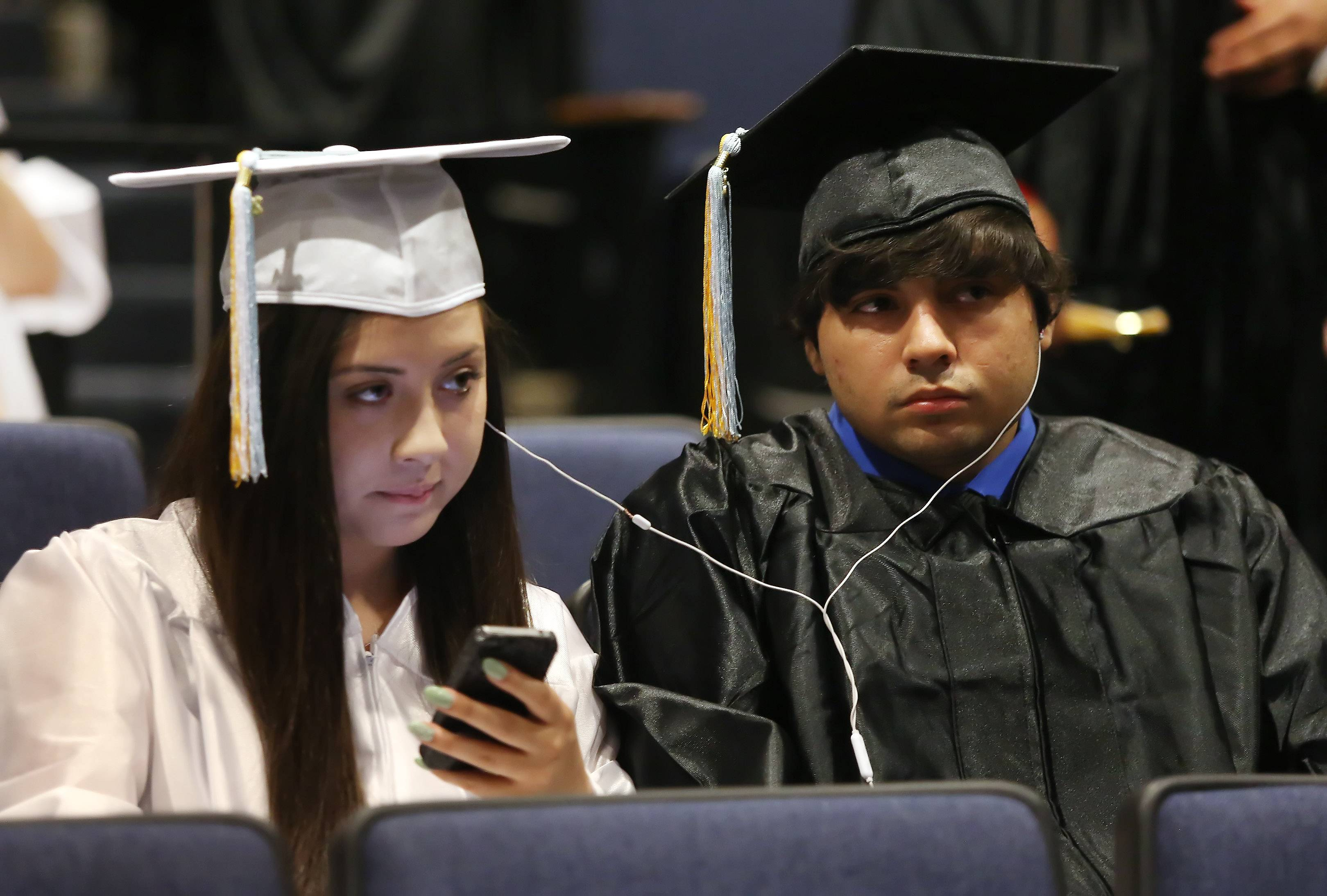 Amanda Salazar, left, and Alex Gonzalez listen to the Chicago Cubs game together during the Maine West High School graduation on Sunday in Des Plaines. Over 500 seniors received their diplomas in the outdoor commencement ceremony.