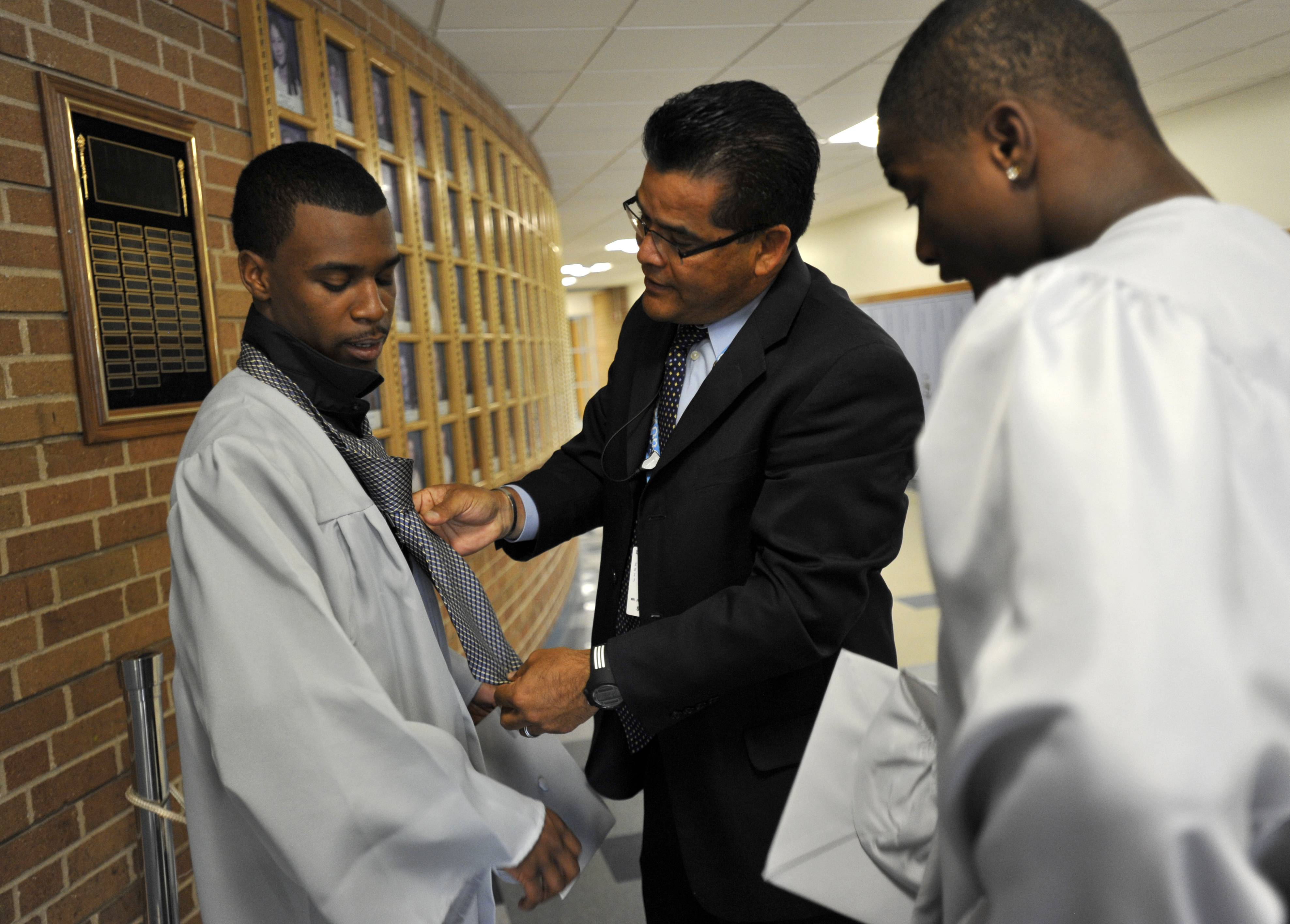 Julio Delreal, Dean of Students (center) helps Marquis Burnett (left) put on a tie before the Willowbrook High School commencement on Sunday, June 8, at the school in Villa Park. Jaquise Williams is on the right.