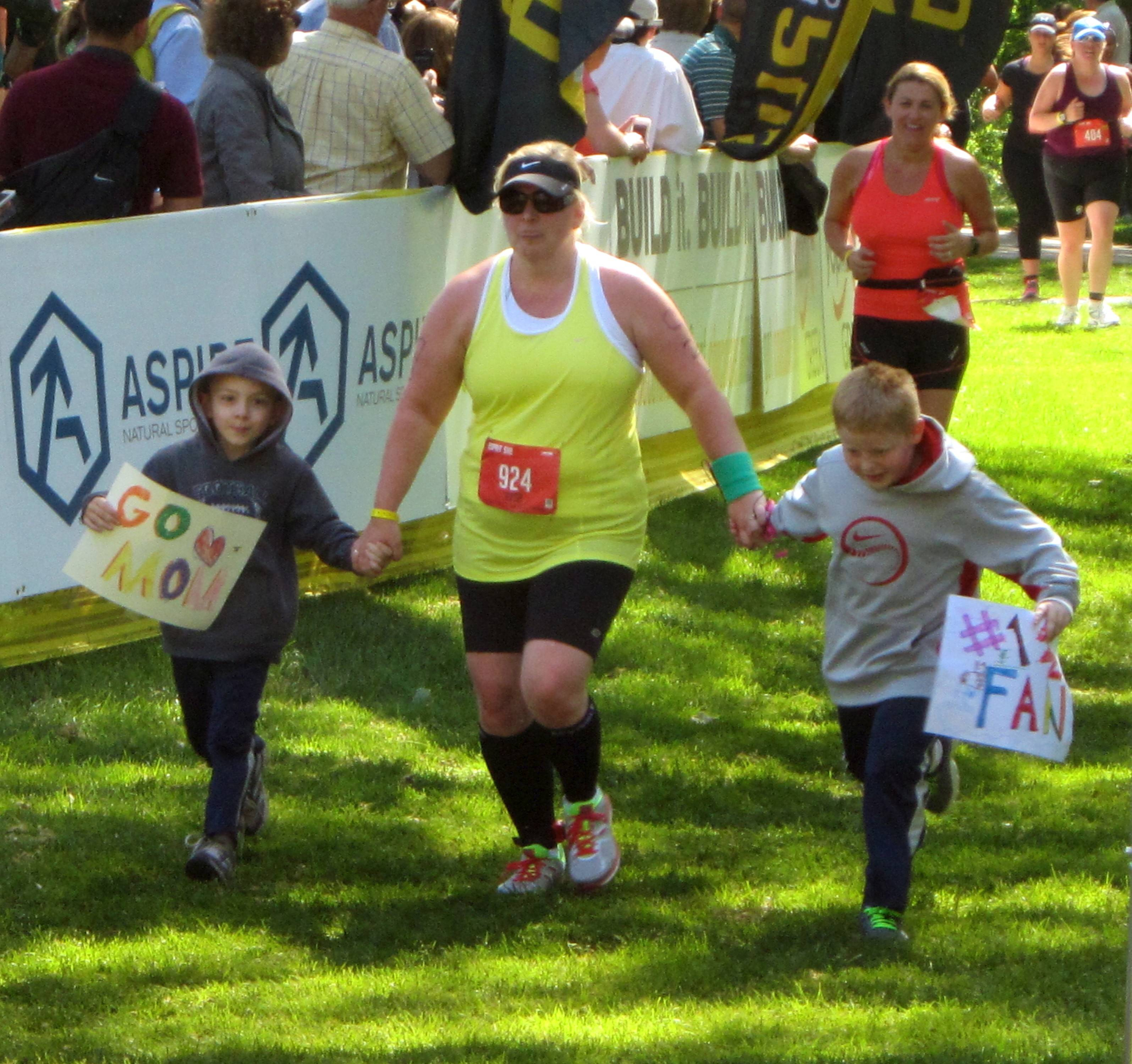 One triathlon participant brings her children with her as she crosses the finish line Sunday in the annual Esprit de She Triathlon in Naperville. The women-only triathlon included more than 1,500 athletes.