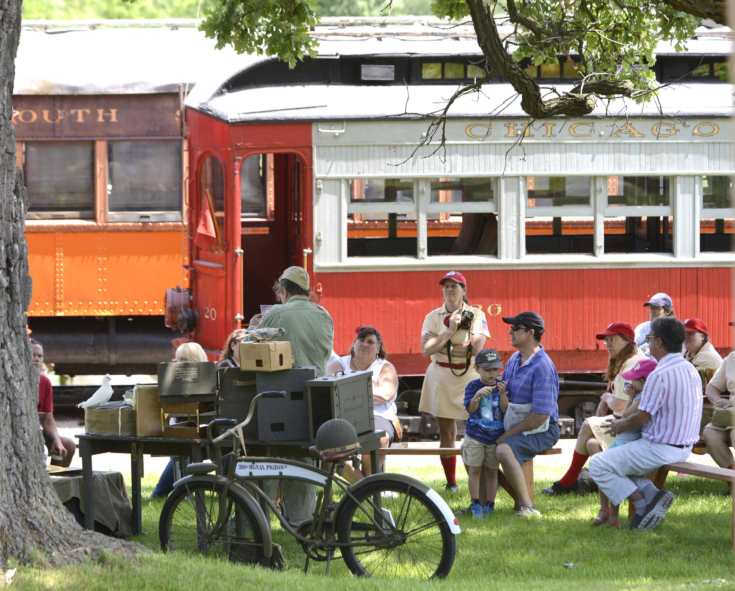 "Surrounded by historical trains and trolleys, people listen to a presentation Sunday at the Fox River Trolley Museum's ""Rails To Victory"" World War II Living History Re-enactment in South Elgin."