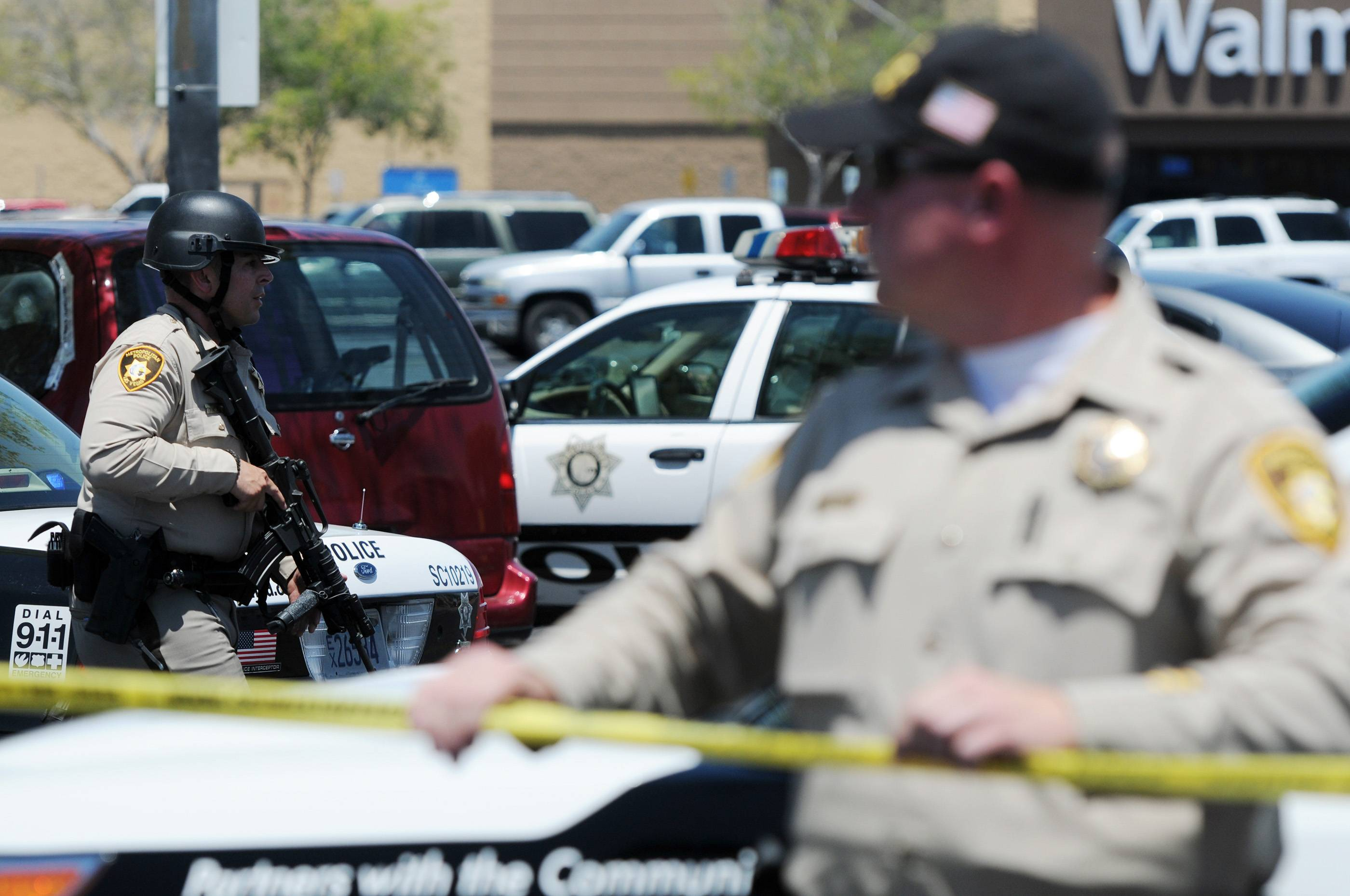 Las Vegas police officers are near the scene of a shooting Sunday in Las Vegas. The spree began around 11:30 a.m. Sunday when a man and woman walked into CiCi's Pizza and shot and killed two officers who were eating lunch, Las Vegas police spokesman Larry Hadfield said.
