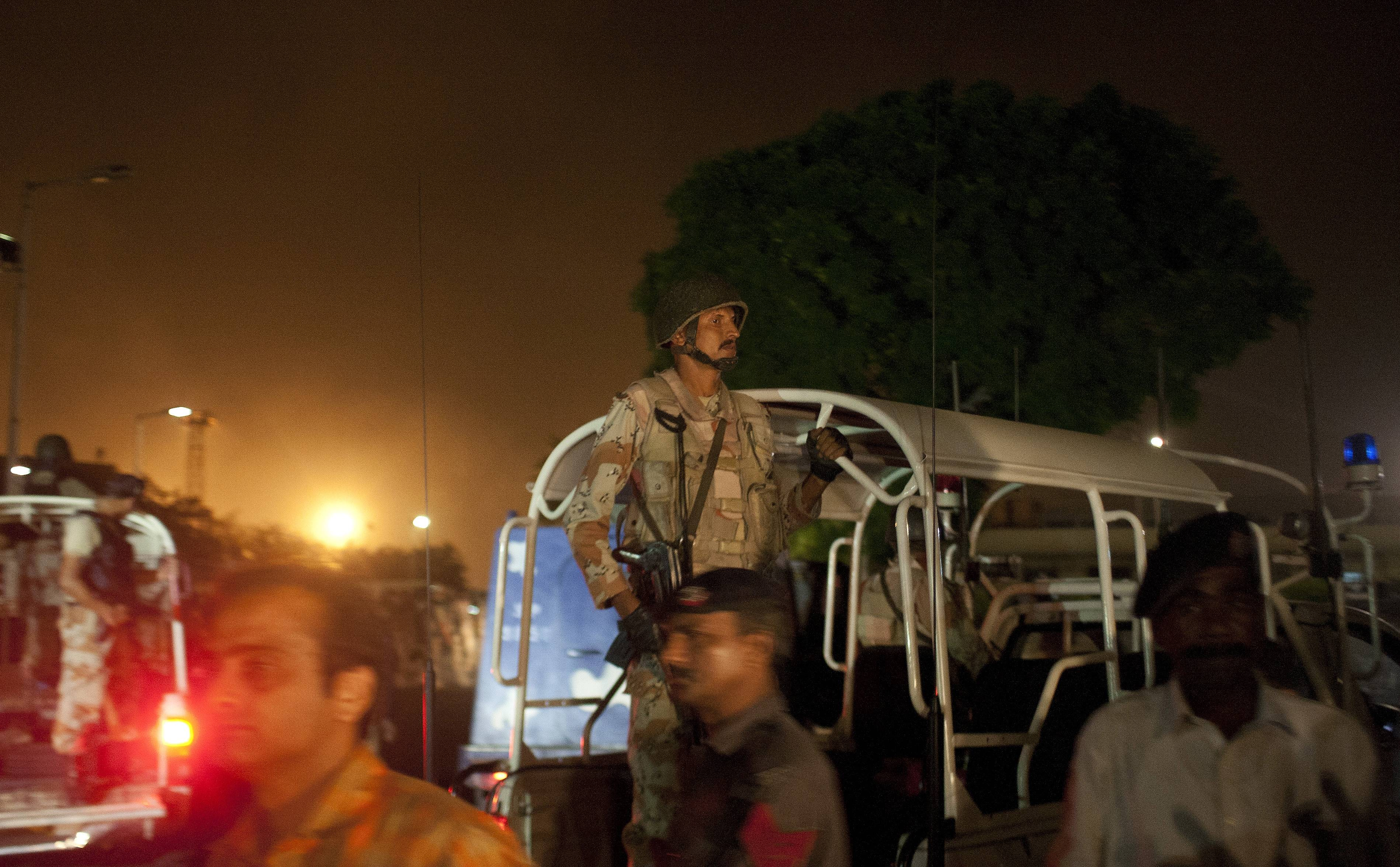 Pakistani security troops rush to Karachi airport terminal following attacks by unknown gunmen on Sunday night in Pakistan. Gunmen stormed an airport terminal used for VIPs and cargo in Pakistan's largest city on Sunday night, killing and wounding scores of people, officials said.