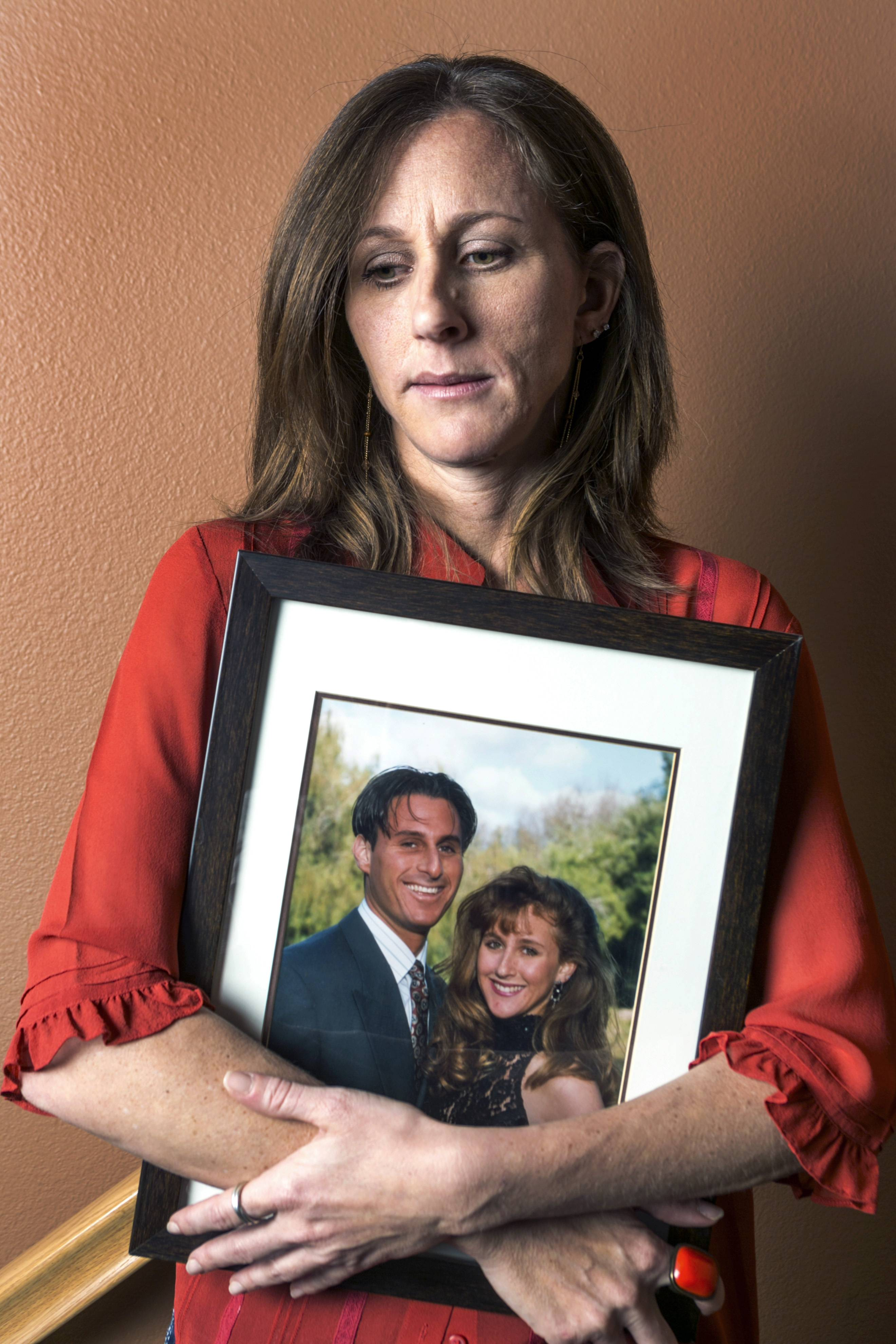 Kim Goldman holds a photo of her with her late brother, Ronald Goldman, murdered with his friend Nicole Brown Simpson in 1994, during an interview at her home in Santa Clarita, Calif. A civil jury awarded the Brown and Goldman families $33.5 million in wrongful death damages, which the Goldmans are still trying to collect.
