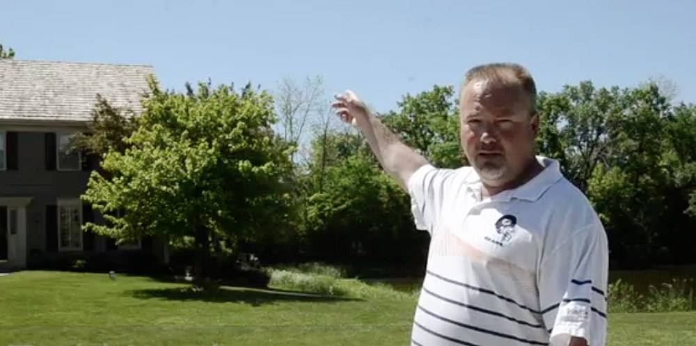Huntington Lakes resident Todd Larak points to where a cellular tower could rise near his house. The proposal has been withdrawn for now but could be refiled in December.