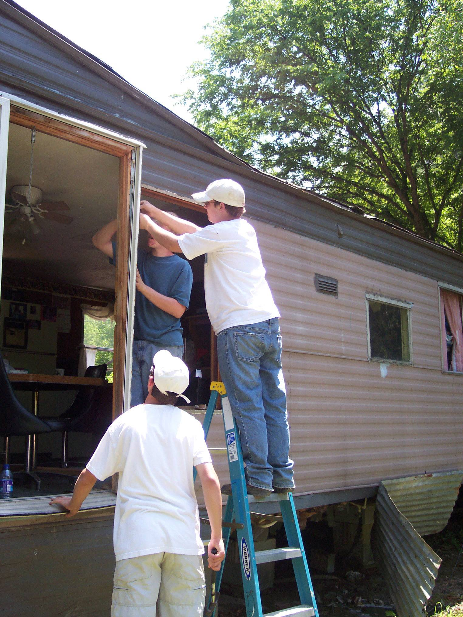 Peter Van Nortwick and Austin Schuetz replace a door in a trailer home last June in Prestonsburg, Kentucky, where high school students from St. Charles Episcopal Church spend a few days each June repairing homes on a mission trip called Mission in the Mountains.