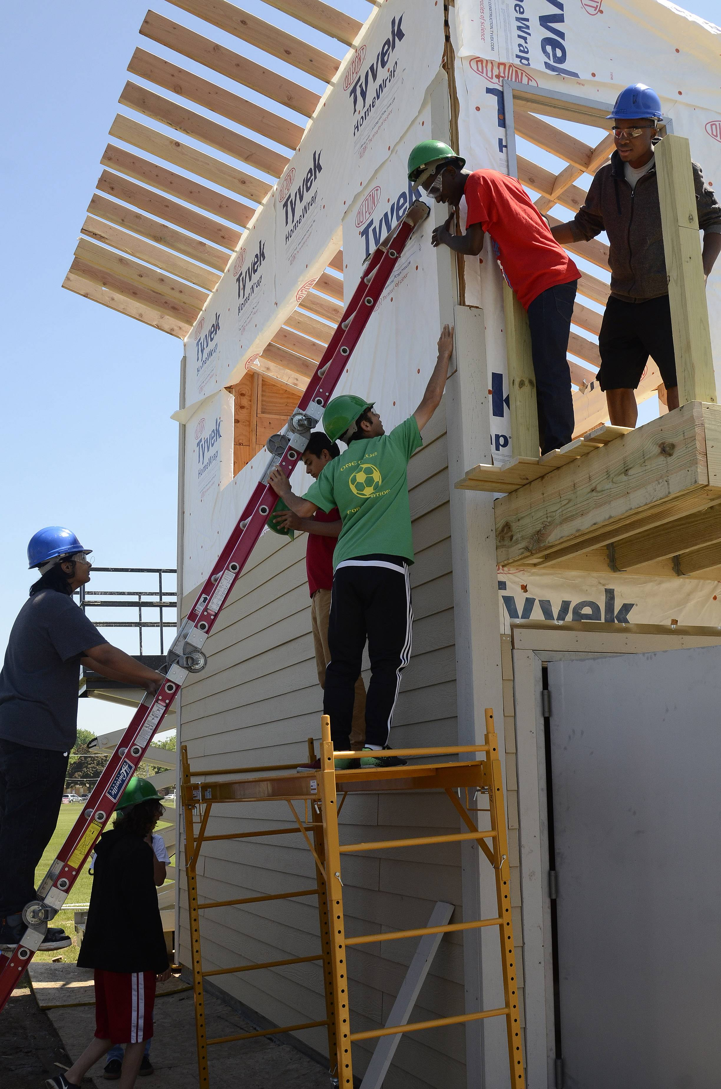 Maine East High School students enrolled in a geo-construction class put the finishing touches on a press box behind the school's varsity baseball diamond.