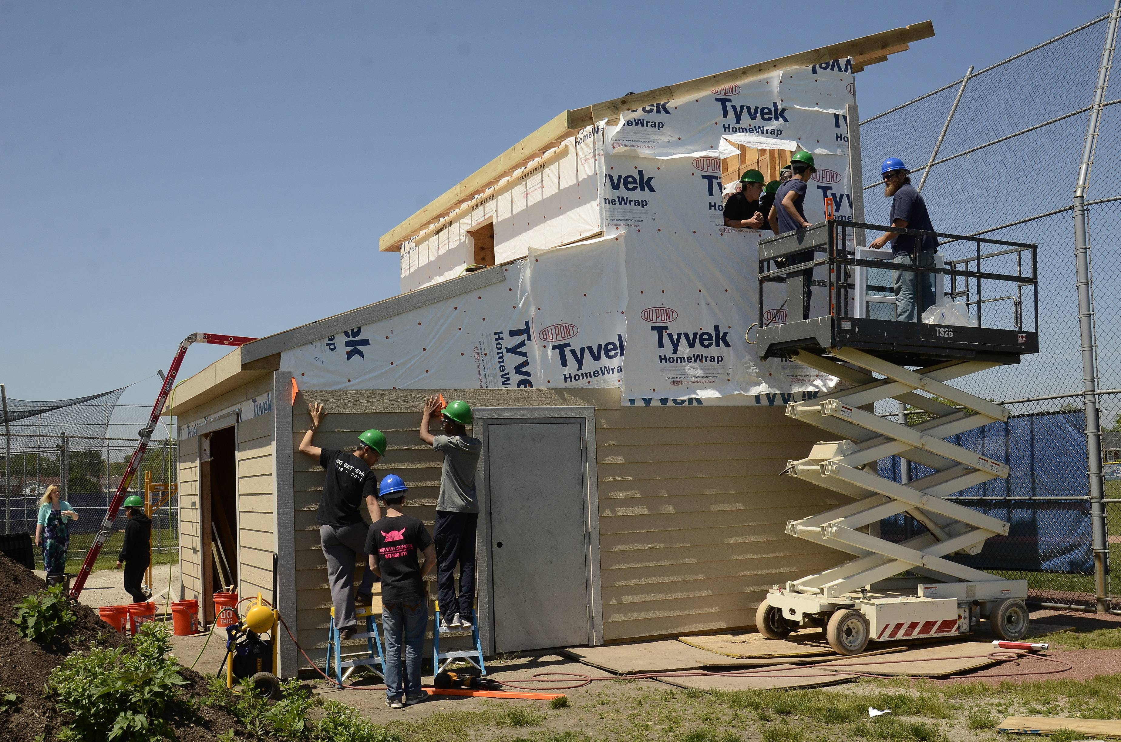 Students in a Maine East High School geo-construction class work on a two-story press box behind the school's baseball diamond.