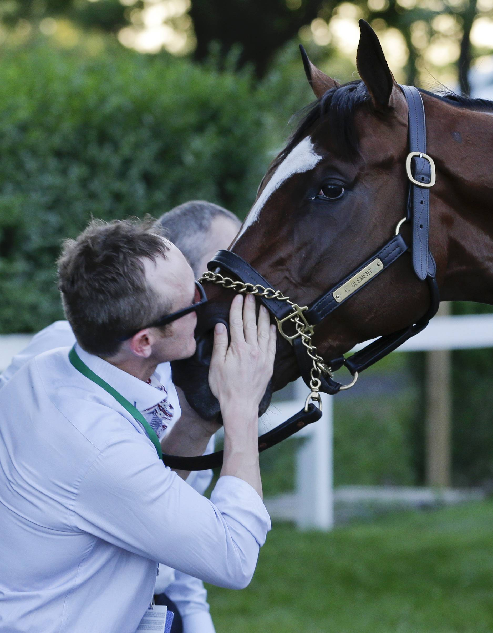 Exercise rider Lee Vickers kisses California Chrome after he finished fourth in the Belmont Stakes horse race, Saturday, June 7, 2014, in Elmont, N.Y.