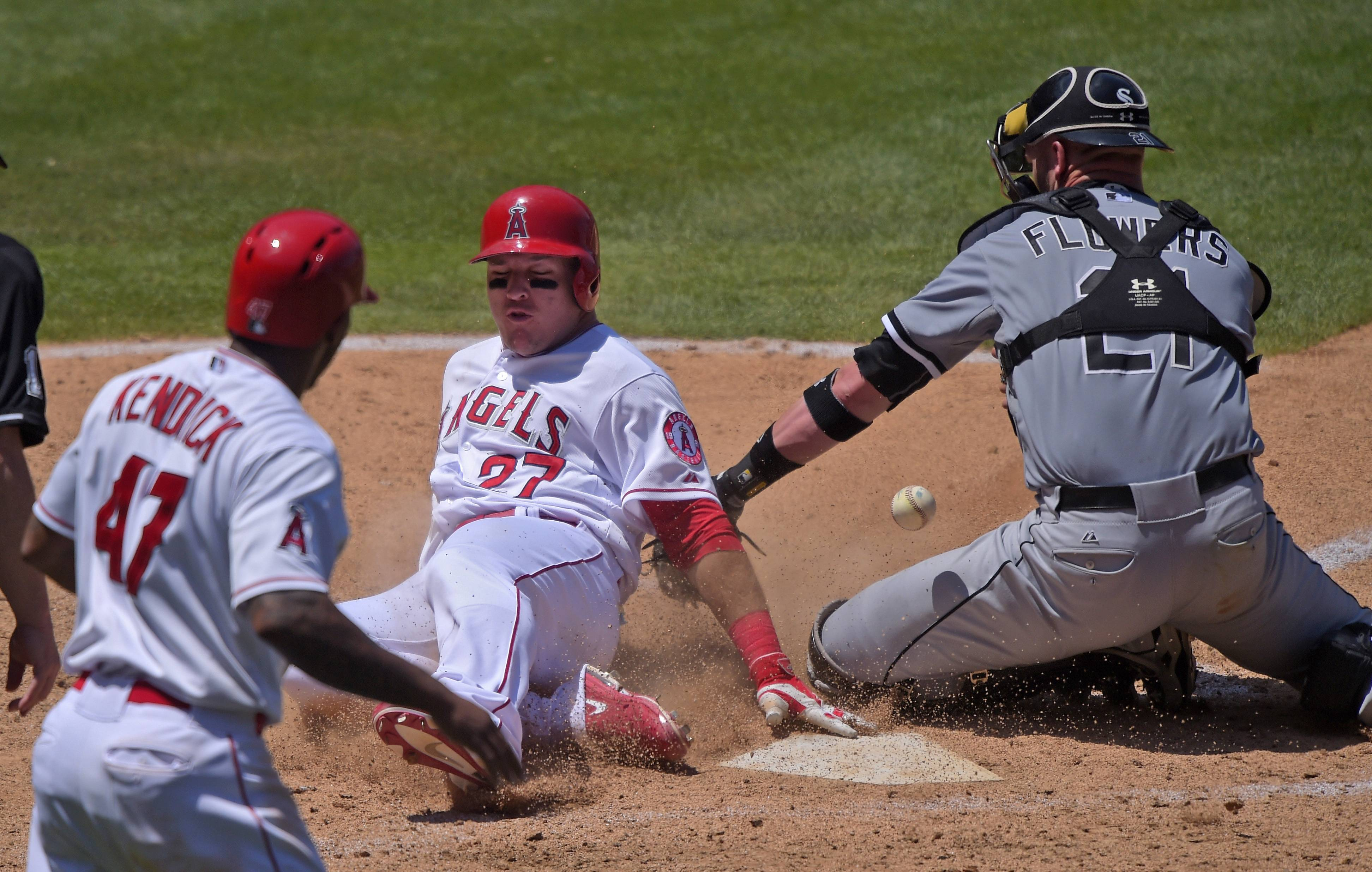 Los Angeles Angels' Mike Trout, center, scores on an RBI double by Josh Hamilton as Chicago White Sox catcher Tyler Flowers, right, loses the ball and Howie Kendrick looks on as during the fifth inning of a baseball game, Sunday, June 8, 2014, in Anaheim, Calif.
