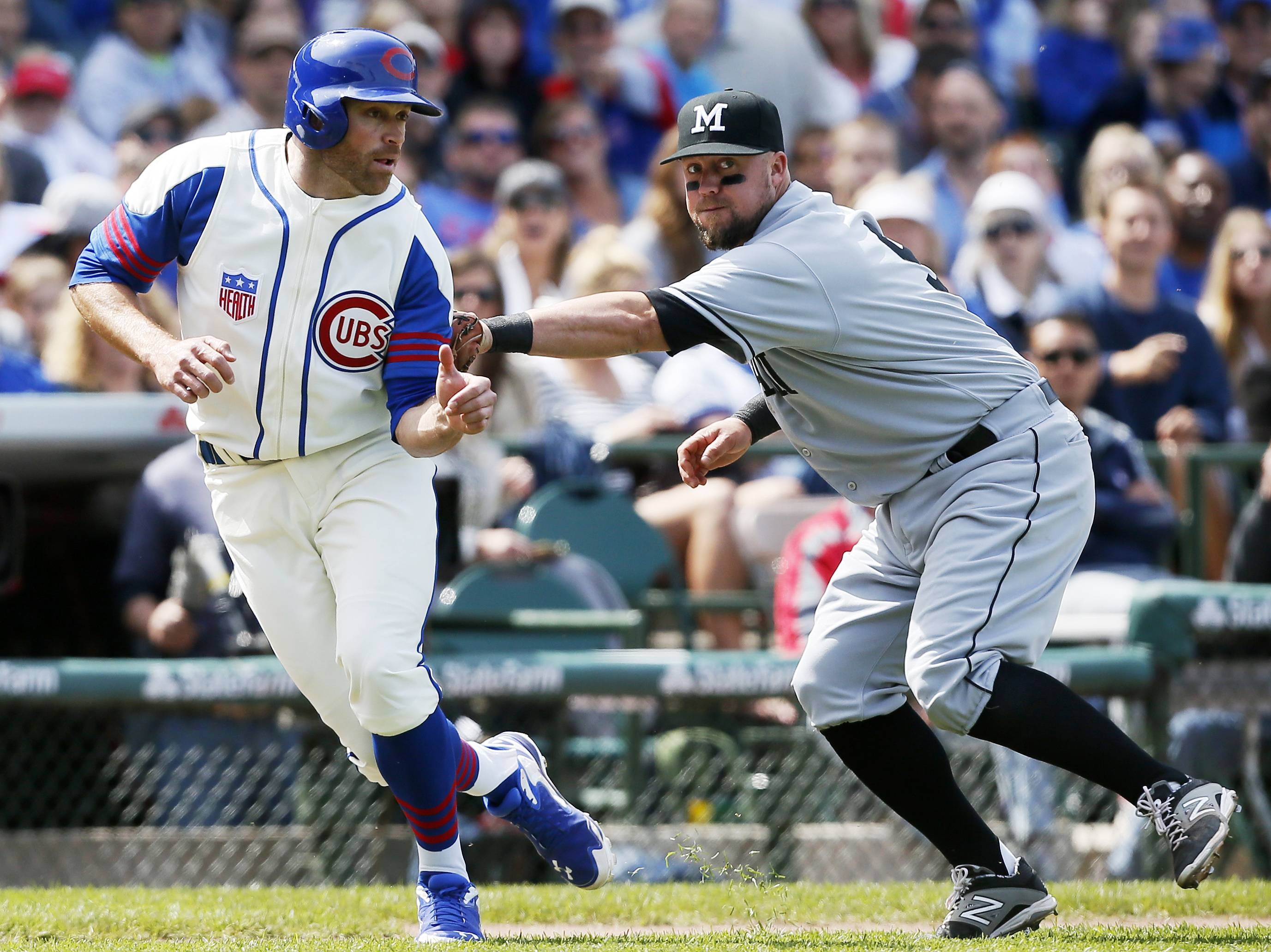The Cubs' Nate Schierholtz, left, is tagged out by Miami Marlins third baseman Casey McGehee on a run down during the sixth inning of a baseball game on Sunday, June 8, 2014, at Wrigley Field.